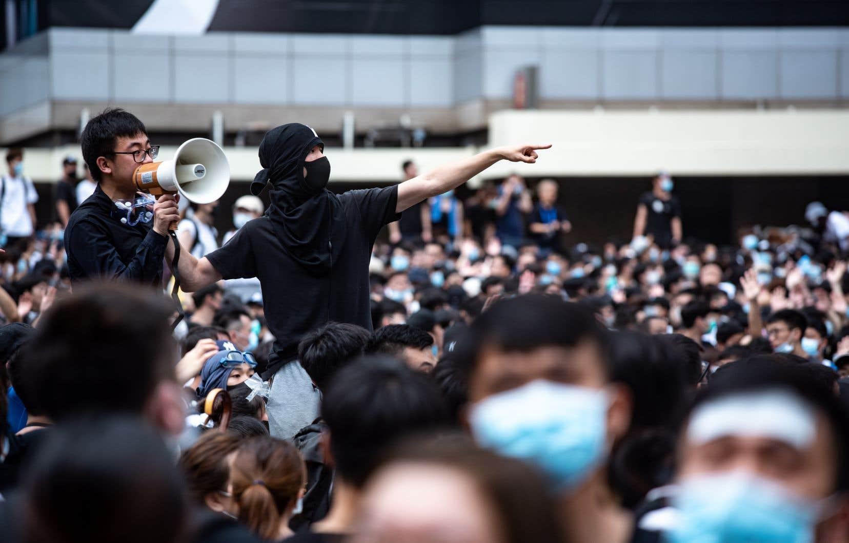 Des milliers de protestataires vêtus de noir, pour la plupart des jeunes gens, encerclaient les bâtiments du gouvernement dans le centre de l'île de Hong Kong et paralysaient la circulation pour exiger le retrait du projet soutenu par Pékin.