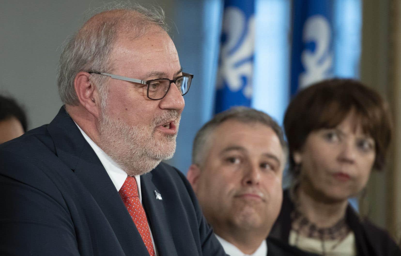 Le chef par intérim du Parti libéral, Pierre Arcand, devant ses collègues libéraux Sébastien Proulx et Hélène David