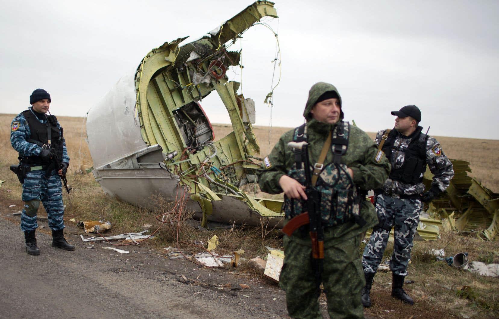 Sur cette photo datée de novembre 2014, des soldats russes protègent l'épave de l'avion MH17, percuté par un missile en juillet 2014, pendant que des enquêteurs néerlandais menaient leur fouille.