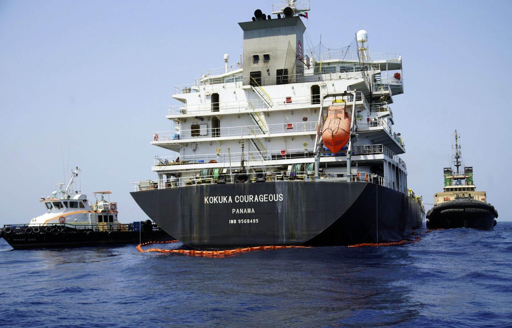 Amarré au port de la base navale américaine à Fujairah, dans les Émirats arabes unis, le Kokuka Courageous est entouré d'une barrière flottante de couleur orange, afin de retenir d'éventuelles fuites.