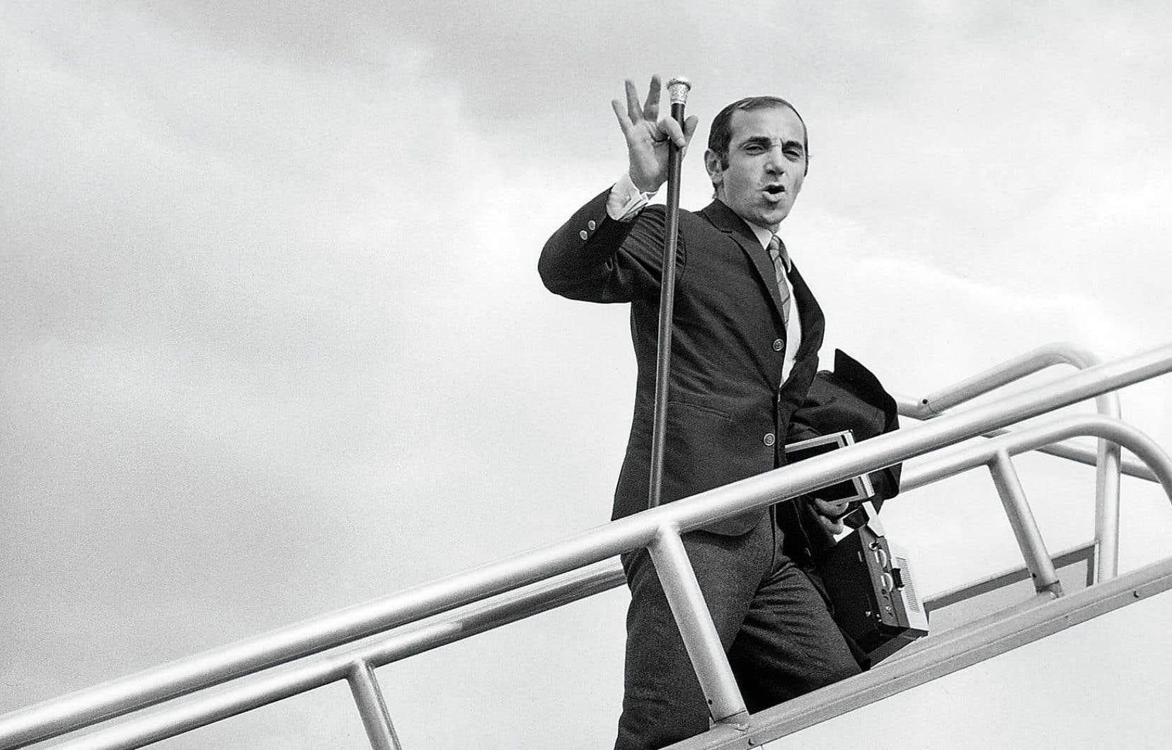 Charles Aznavour montant à bord d'un avion en partance pour le Mexique, le 17 septembre 1966