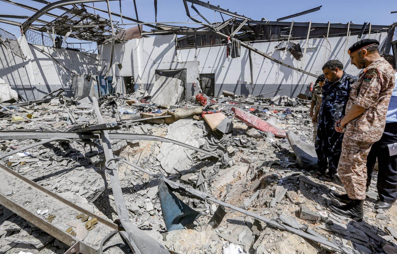Des militaires libyens du gouvernement d'union nationale regardent les débris du centre de détention de migrants attaqué mardi.