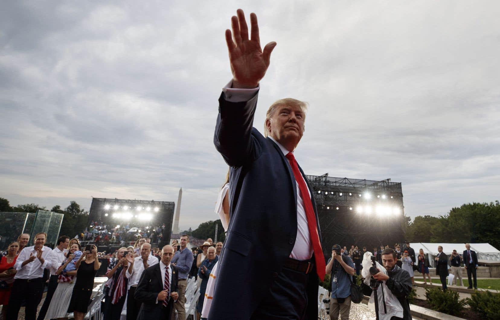 Le président Donald Trump salue la foule alors qu'il quitte la célébration de la fête de l'indépendance devant le Lincoln Memorial à Washington.