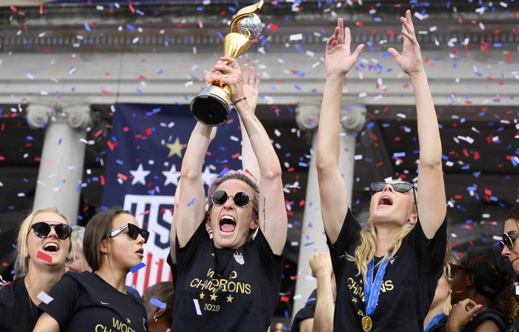 La joueuse de soccer américaine Megan Rapinoe (centre) et d'autres membres de l'équipe célèbrent avec leur trophée devant l'hôtel de ville de New York le 10 juillet 2019.