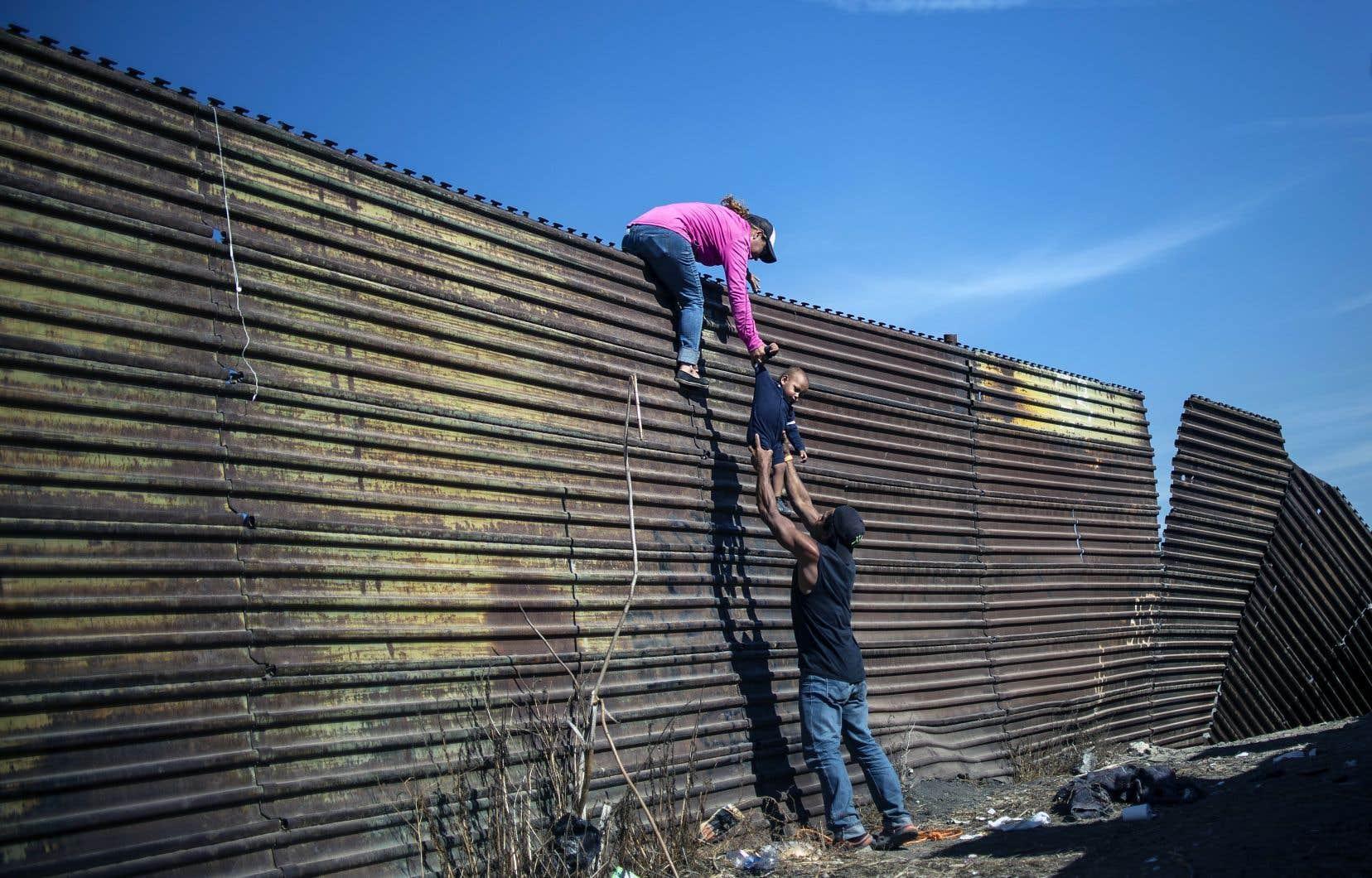 Des immigrants d'Amérique centrale grimpant la séparation entre le Mexique et les États-Unis, en novembre dernier
