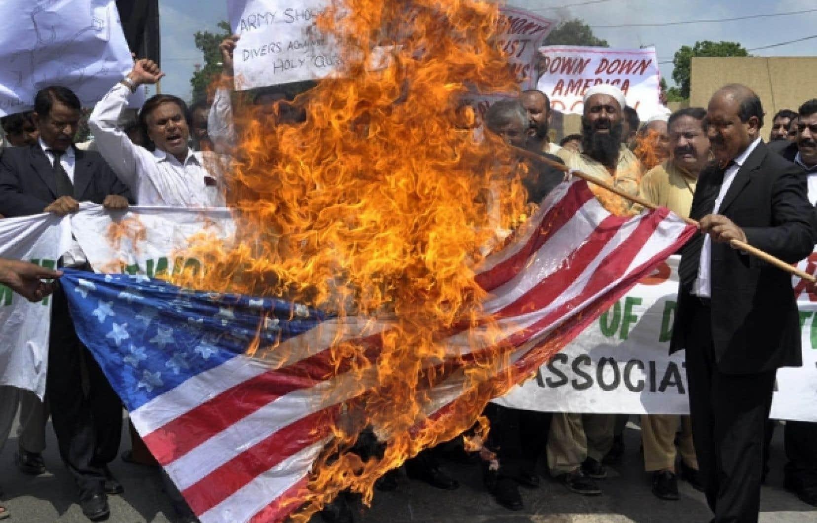Des manifestants ont brûlé un drapeau des États-Unis hier, à Ahmedabad, en Inde.<br />