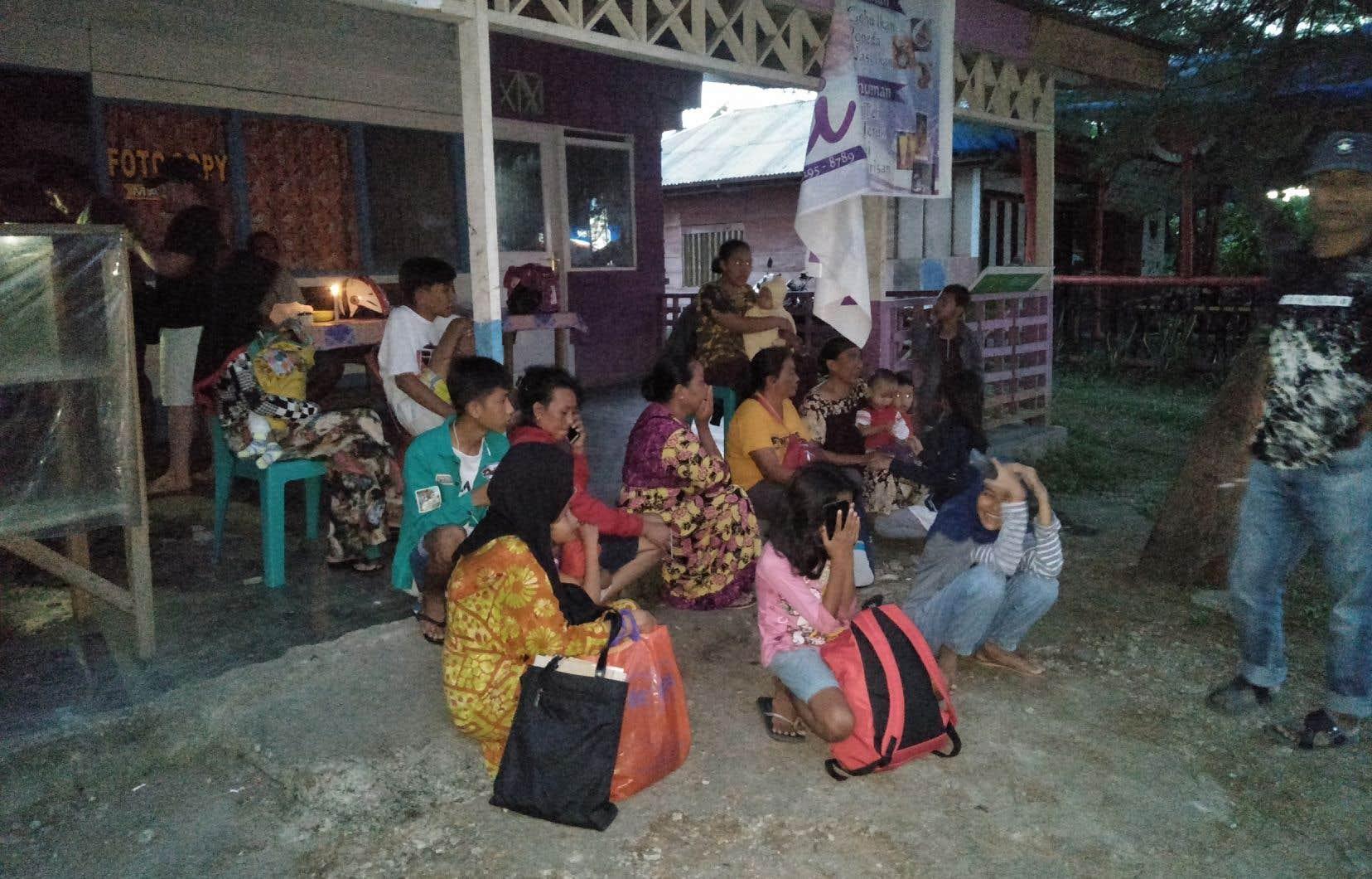 Des résidents se tiennent à l'écart de leurs maisons après le séisme à Labuha.