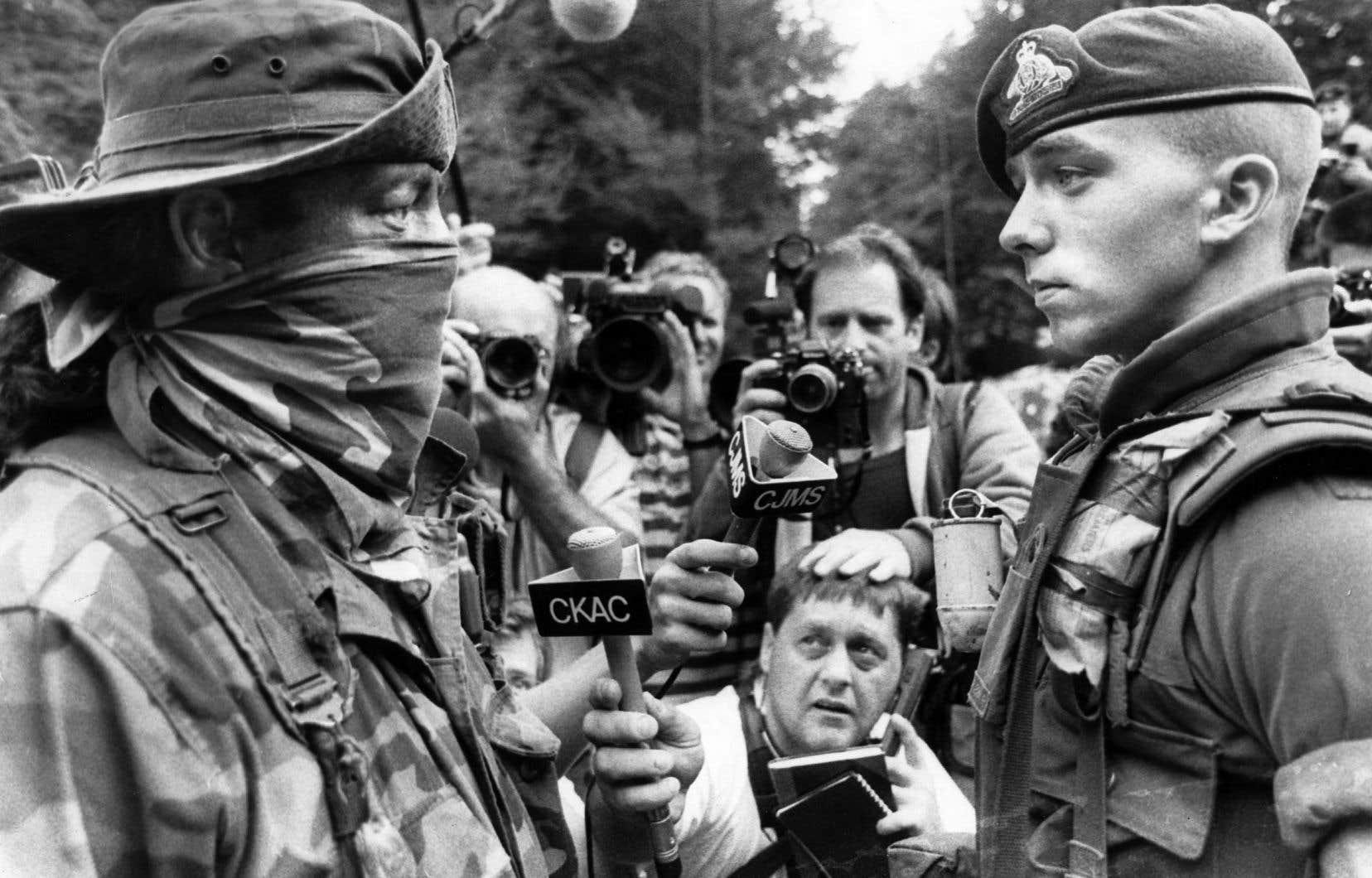 Un membre des Warriors, un groupe militant pour les droits territoriaux des Mohawks, et un soldat de l'armée canadienne se défient devant un rassemblement de médias, le 10 septembre 1990, en pleine crise d'Oka.