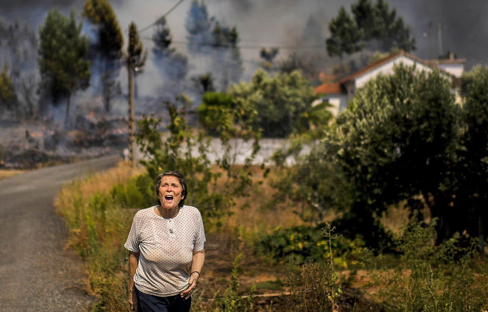 Une femme crie pour demander de l'aide à l'approche des flammes dans le village de Macao, au Portugal.