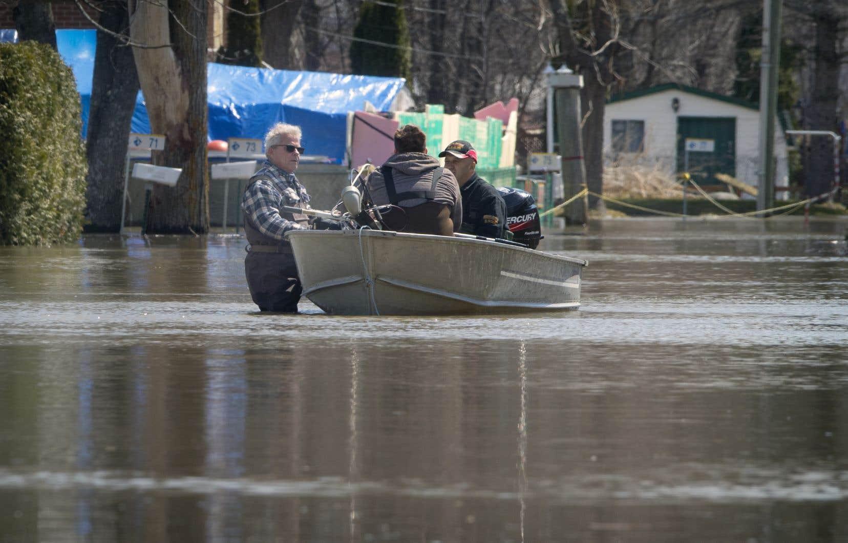 Des hommes en chaloupe lors des dernières inondations printanières, à Rigaud