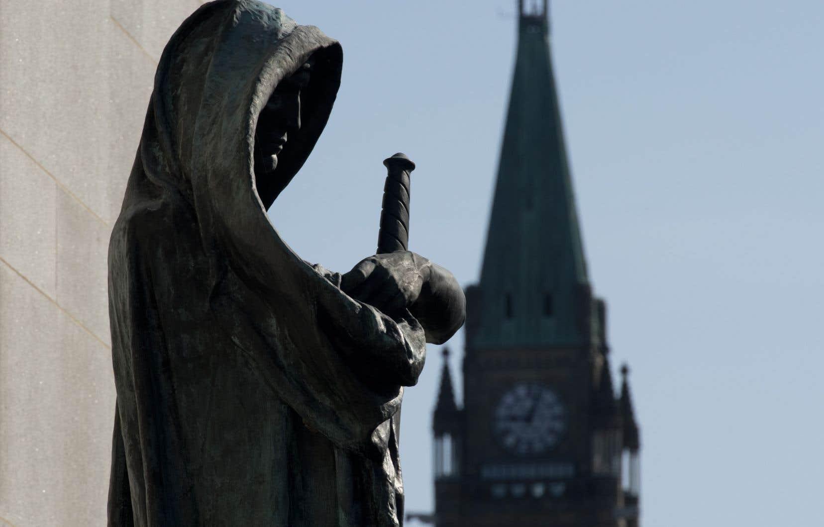 Vue sur la statue Veritas à l'entrée de la Cour suprême du Canada, alors que la tour de la paix apparaît à l'arrière-plan.