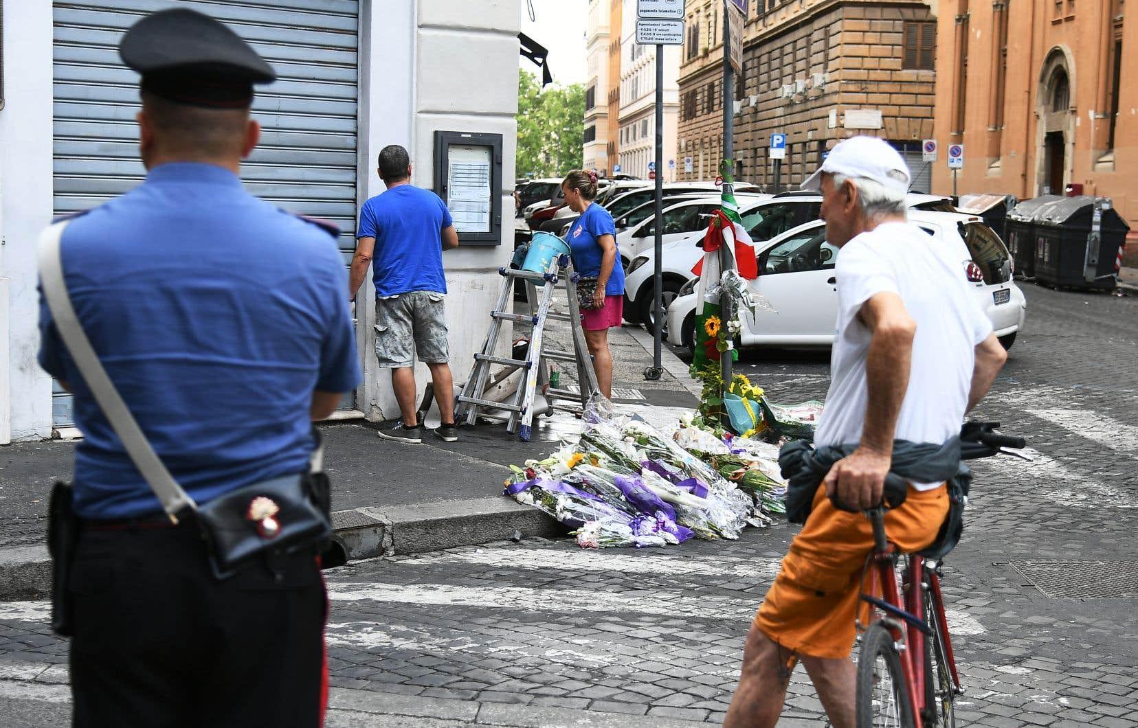 <p>Des citoyens ont constitué un lieu de recueillement spontané en mémoire de Mario Cerciello Rega sous le regard d'un carabinier et d'un homme.</p>