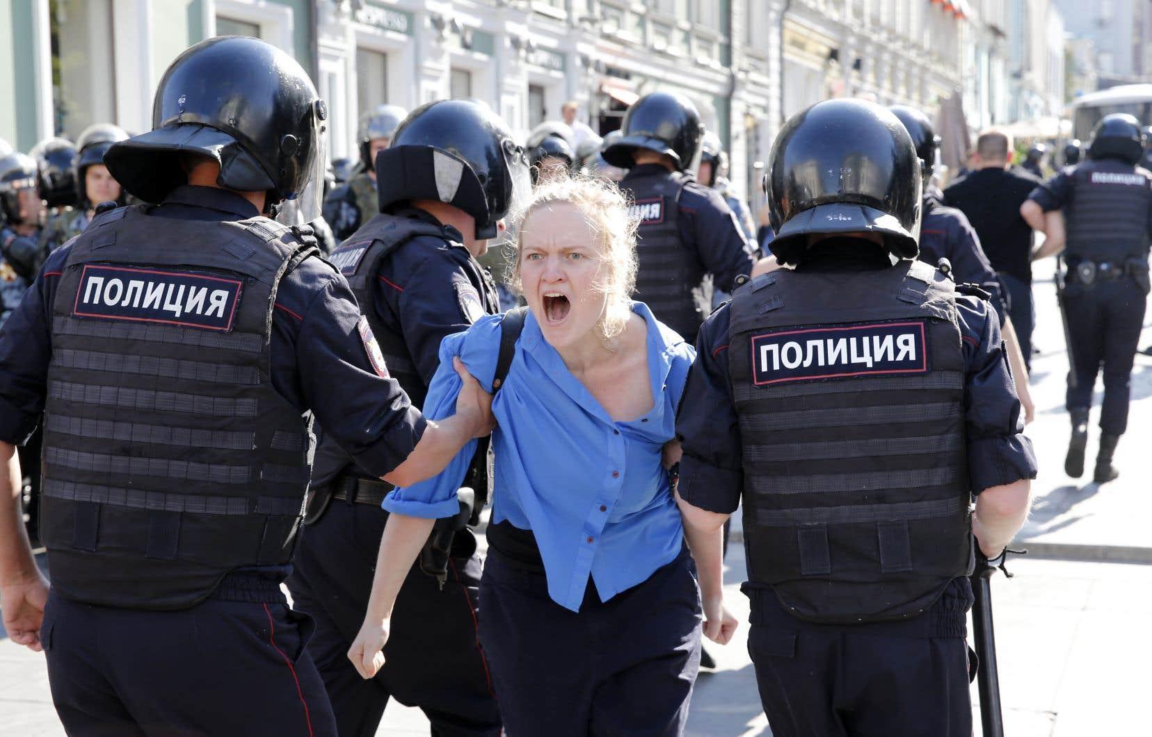 Des policiers arrêtent une manifestante lors d'un rassemblement non autorisé au centre-ville de Moscou, samedi dernier.