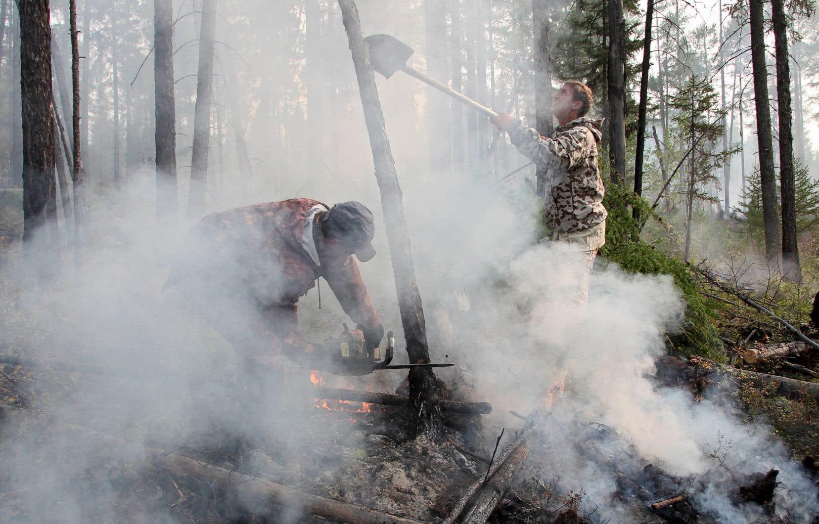 Les pompiers travaillant sur le site d'un feu de forêt dans la région d'Irkoutsk, en Sibérie orientale