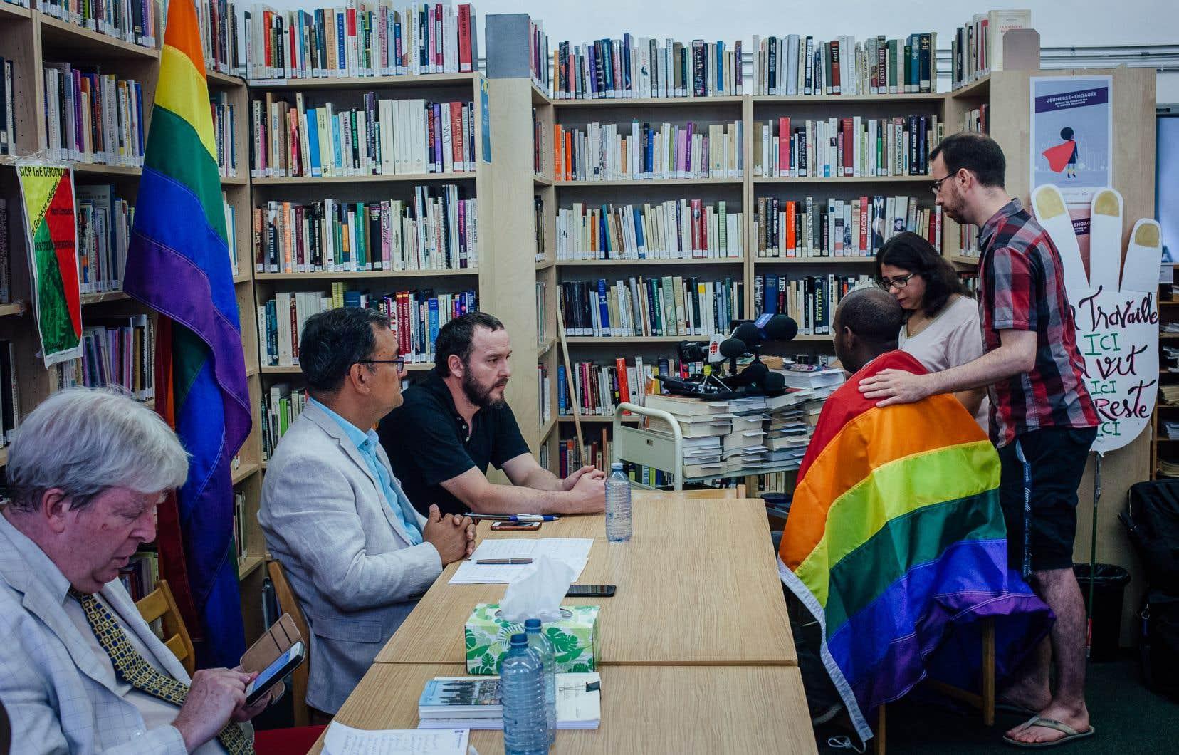 Des groupes de défense des droits de la communauté LGBTQ ainsi que des immigrants tiennent une conférence de presse concernant le cas d'un Guinéen (de dos sur la photo et portant le drapeau LGBTQ) qui serait menacé dans son pays d'origine en tant que militant politique d'opposition et en tant qu'homme bisexuel.