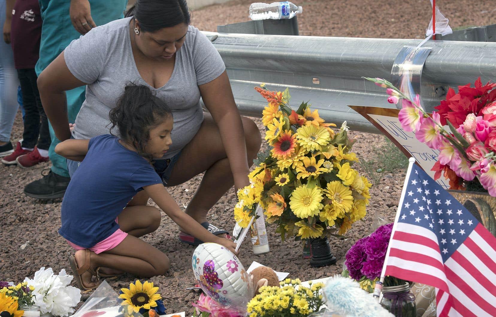 Une famille déposait des fleurs, dimanche, près du Walmart d'El Paso où a eu lieu la fusillade.