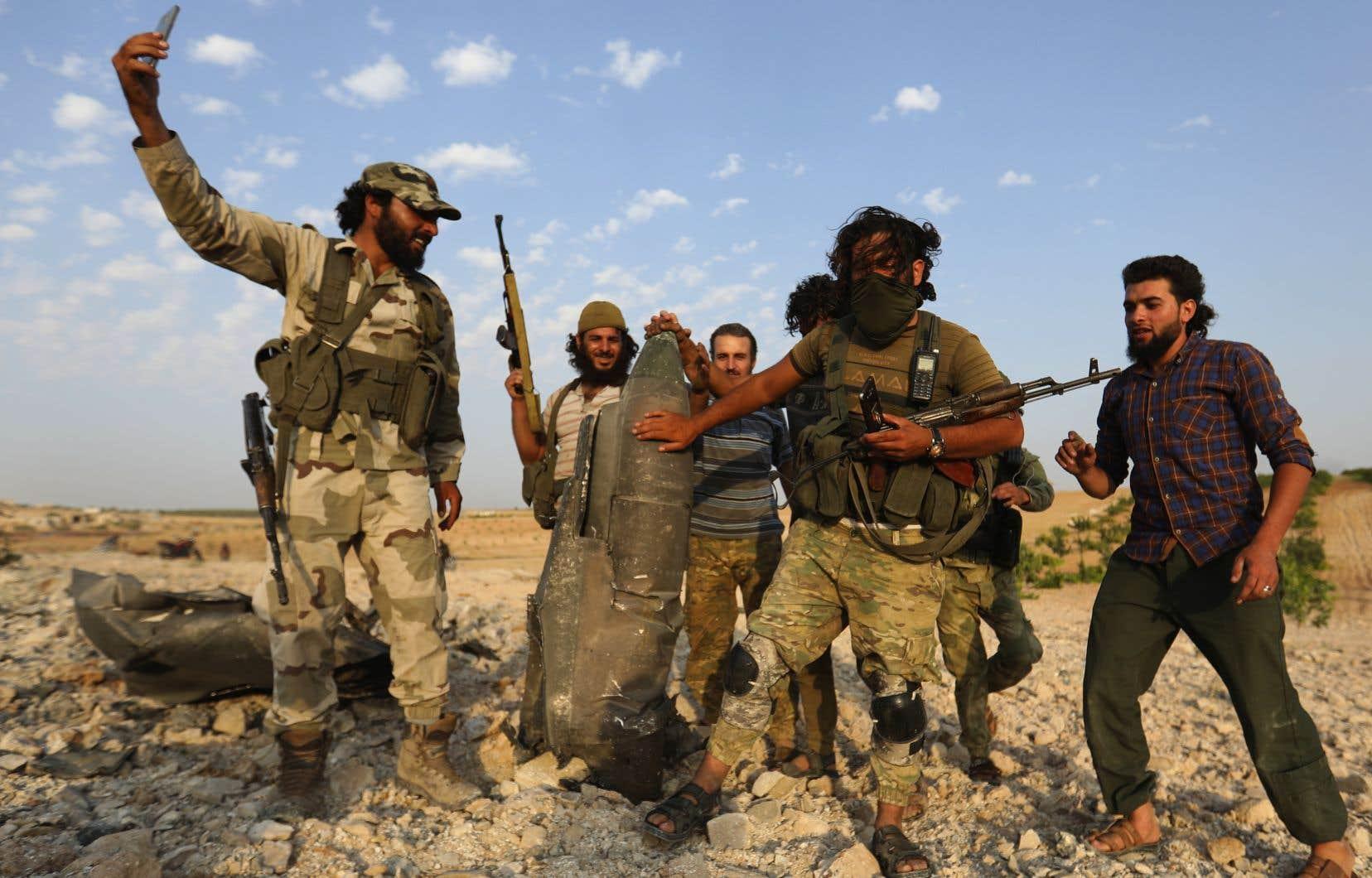 Des combattants rebelles posent avec les restes d'un avion de guerre abattu près Khan Sheikhun, ville tenue par les djihadistes, en Syrie.