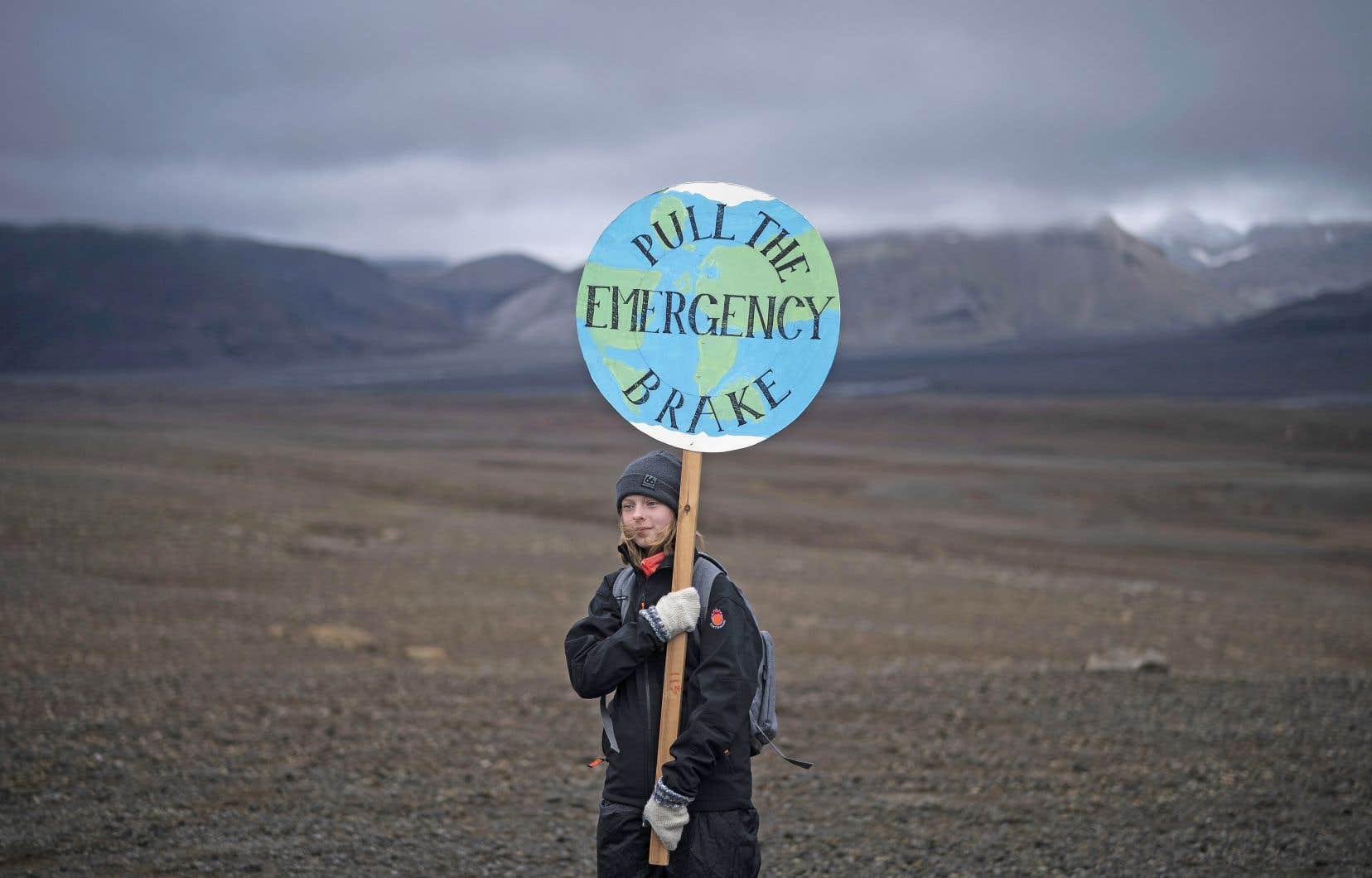 Une jeune fille tenant une affiche sur laquelle il est écrit «tirer le frein d'urgence» lors de la cérémonie tenue dimanche pour souligner la disparition de l'Okjökull