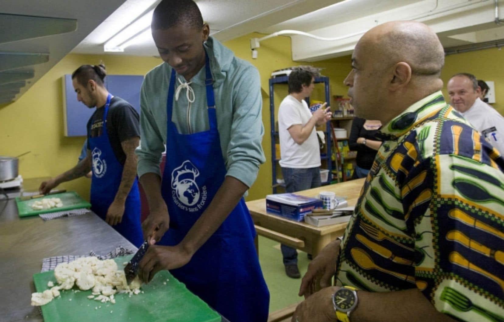 Le chef Jean-Louis Thémis (à droite), fondateur de Cuisiniers sans frontières, initie ses élèves à l'art de la cuisine.<br />