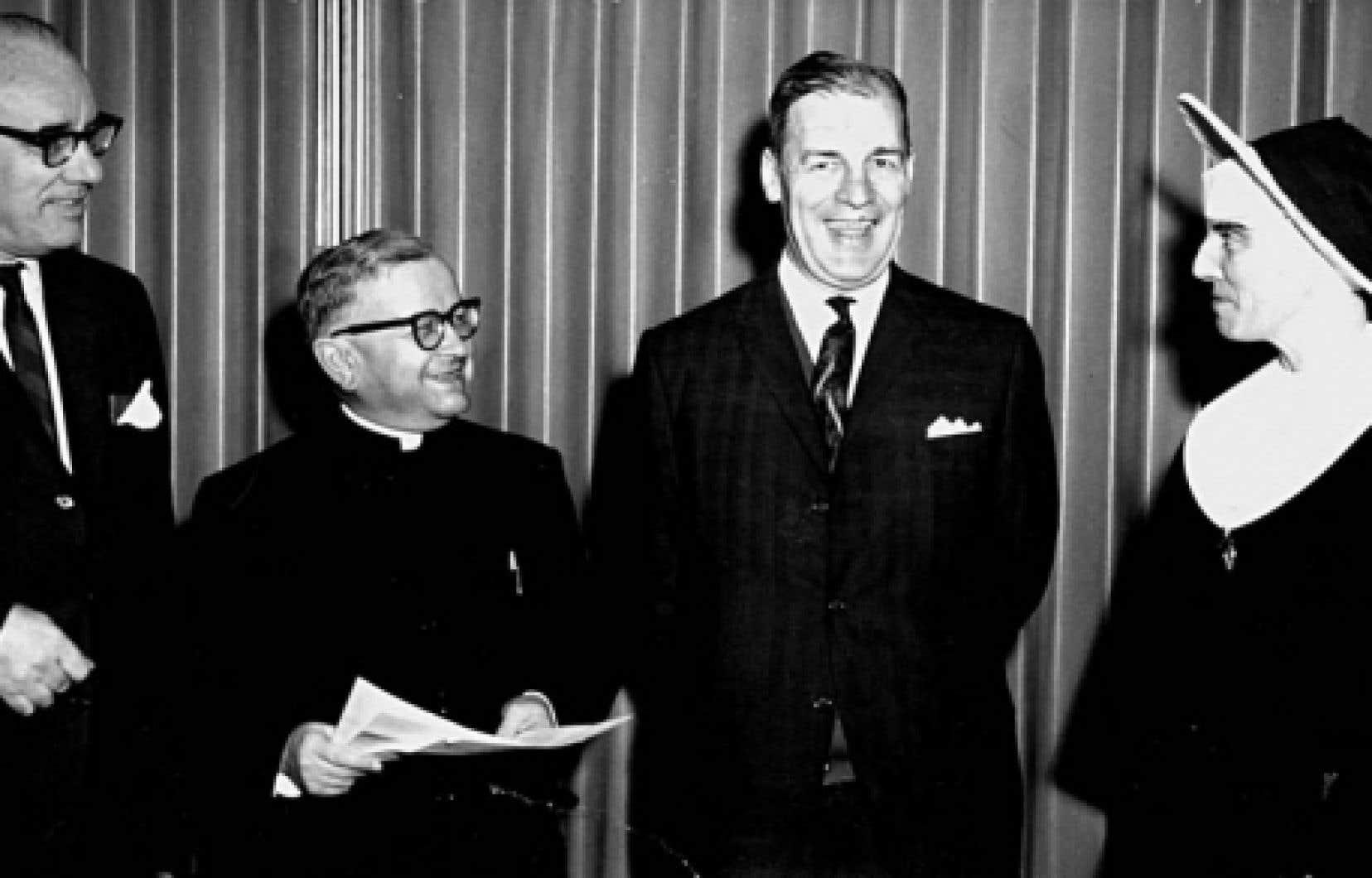 La commission Parent, présidée par Mgr Alphonse-Marie Parent (deuxième à gauche), accouche d'un volumineux rapport: trois tomes répartis en cinq volumes, 1485 pages, 567 recommandations, publiés de 1963 à 1966.<br />