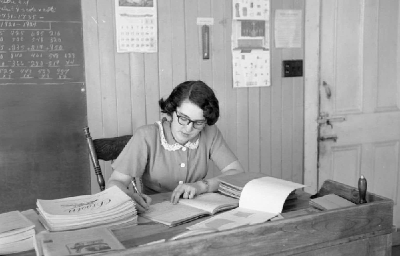 Institutrice corrigeant les travaux des enfants dans une école de rang de Saint-Henri-de-Lévis, en 1952.<br />