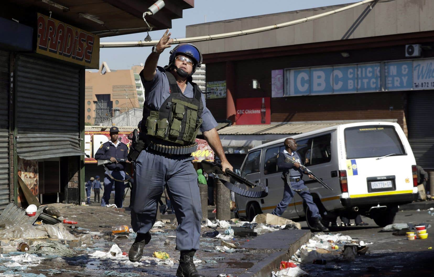 Un policier anti-émeute lance une grenade lacrymogène pour disperser des pilleurs de magasins dans la région de Johannesburg, mardi.