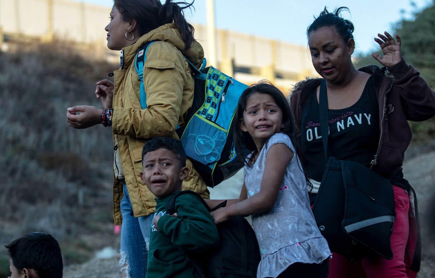 Des enfants pleurent alors qu'un groupe de migrants se rendent aux agents frontaliers américains après avoir franchi la barrière de métal séparant Playas de Tijuana au Mexique des États-Unis.