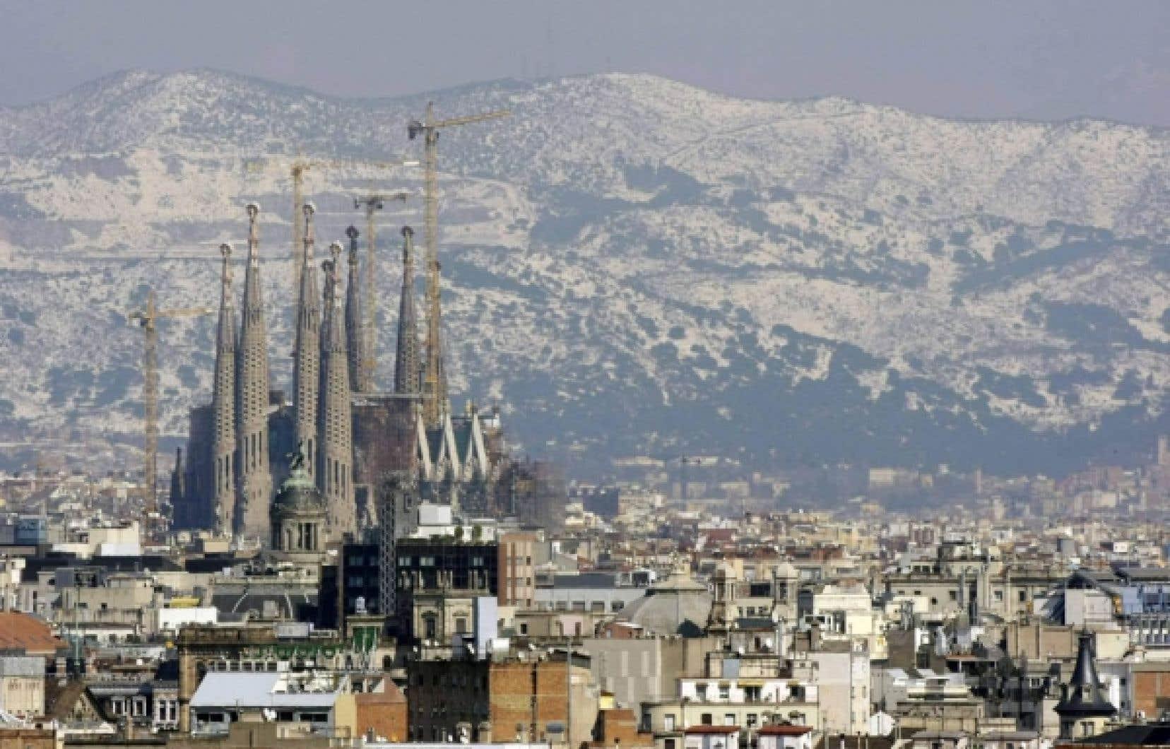 L'église Sagrada Familia de Barcelone, en Espagne, sur fond de montagnes couvertes de neige après une tempête... <br />