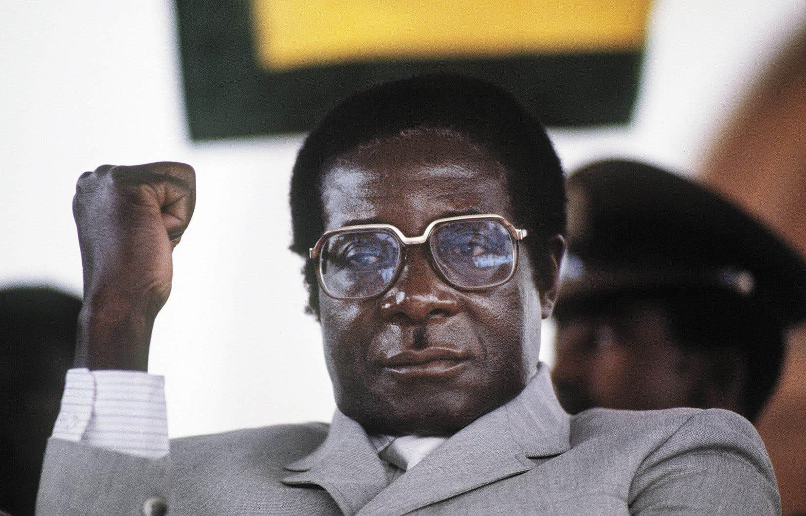 Robert Mugabe brandit son poing dans un amphithéâtre à Harare, en 1984.