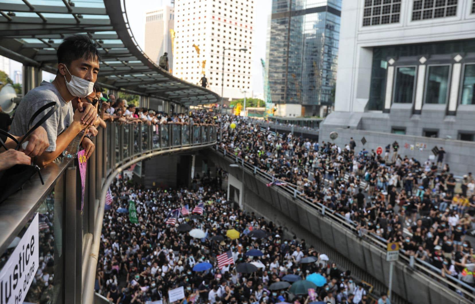 Dans la foule, les parapluies symboliques côtoyaient les drapeaux américains et les pancartes appelant le président Donald Trump à «libérer» Hong Kong.