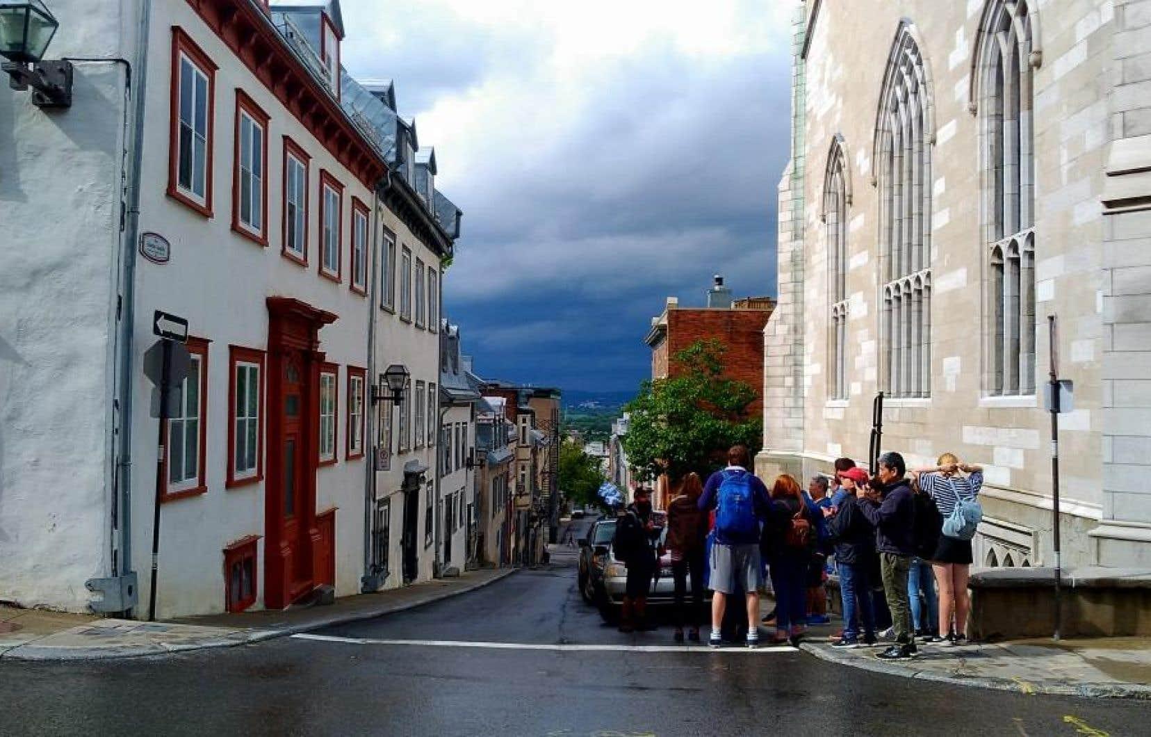 Des touristes longent la rue Dauphine et s'arrêtent au point culminant de la percée visuelle Sainte-Angèle, à Québec.