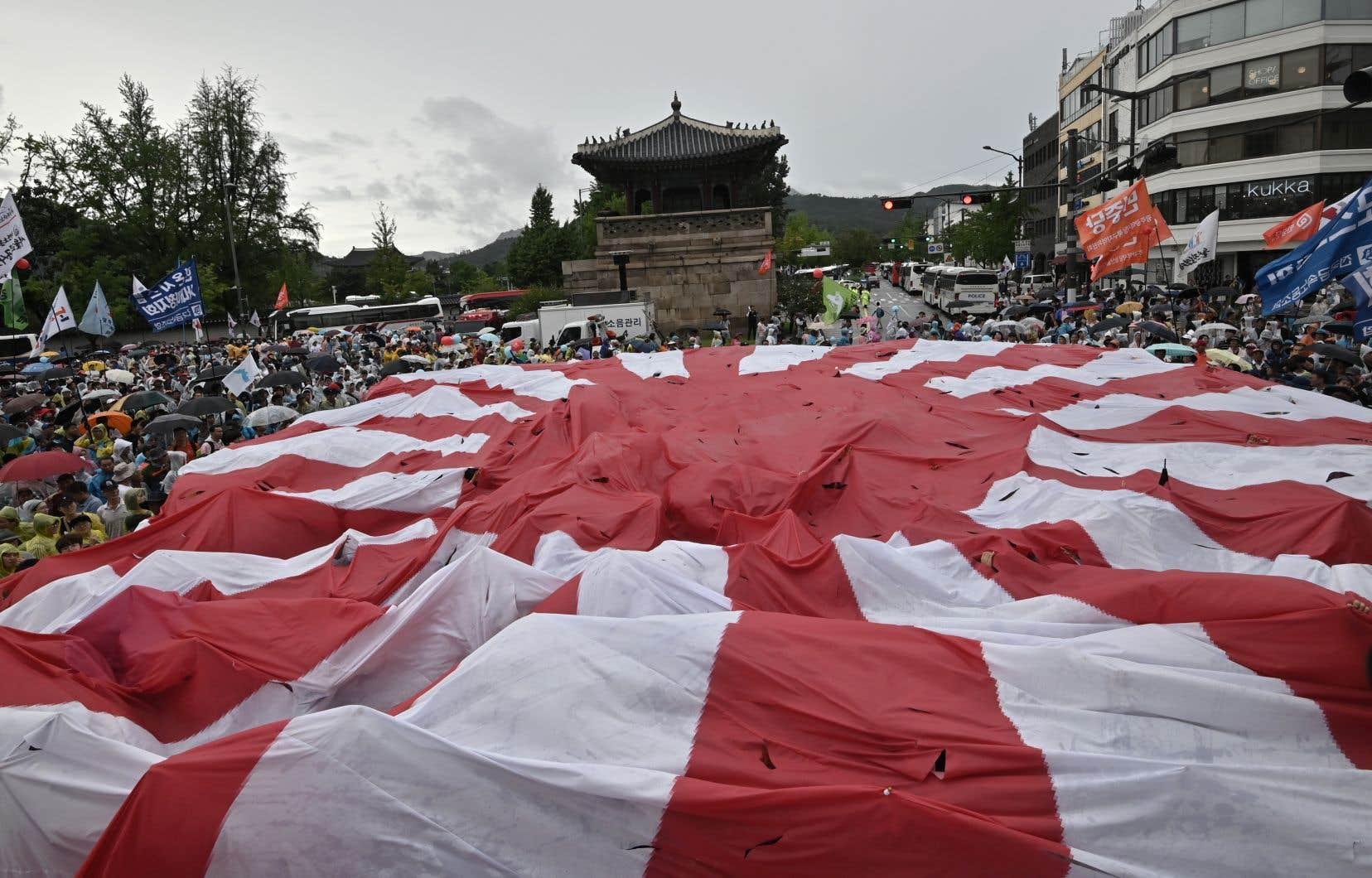 Des manifestants sud-coréens déchirent un énorme drapeau japonais du soleil levant lors d'un rassemblement anti-japonais marquant l'anniversaire de la libération de la Corée du régime colonial japonais de 1910-1945.