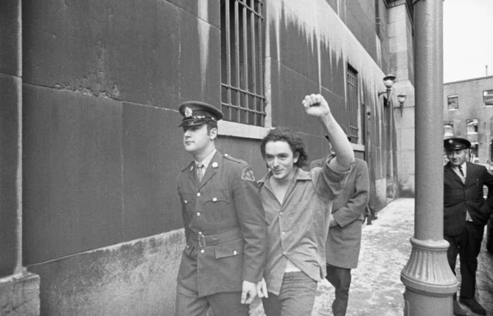 Le 7 janvier 1971, le felquiste Bernard Lortie arrive au palais de justice pour subir son procès. Comme les autres membres de la cellule Chénier, responsable de l'enlèvement de Pierre Laporte, il lève le poing, signe de leur détermination à poursuivre sa lutte.<br />