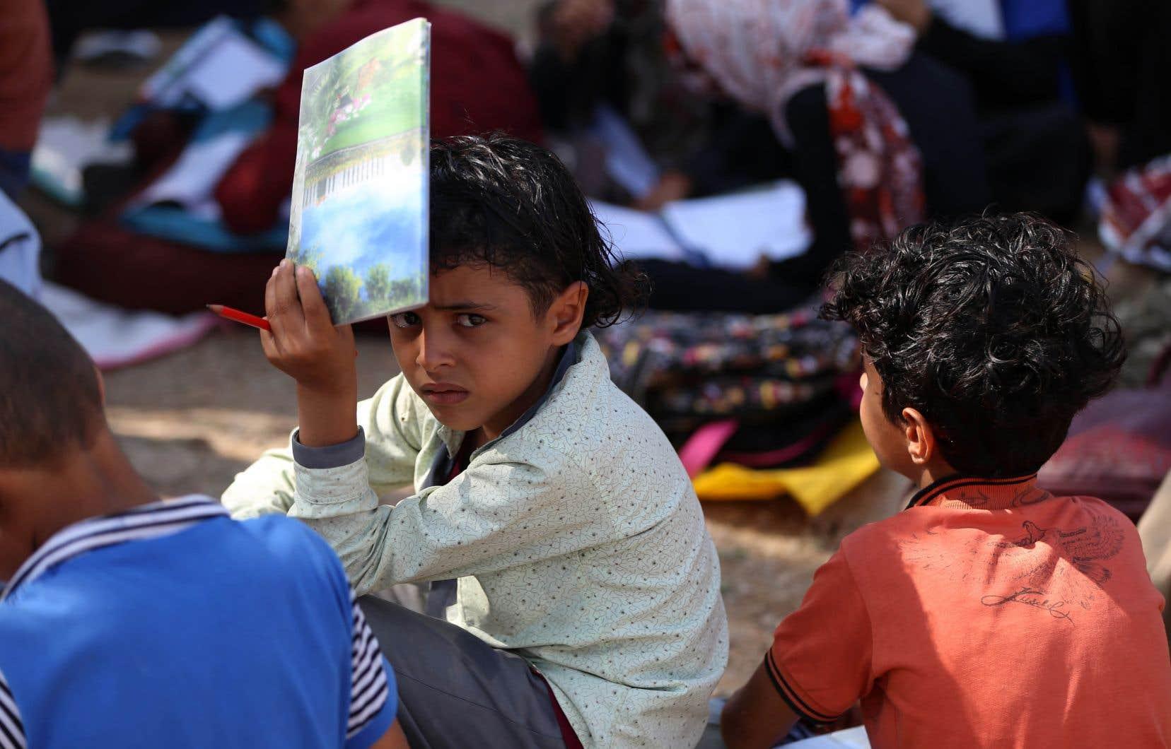 De jeunes enfants participent à une classe en plein air dans le village d'al-Kashar, au Yémen. La construction d'une école pour le village a été interrompue par le début du conflit au pays en 2015.