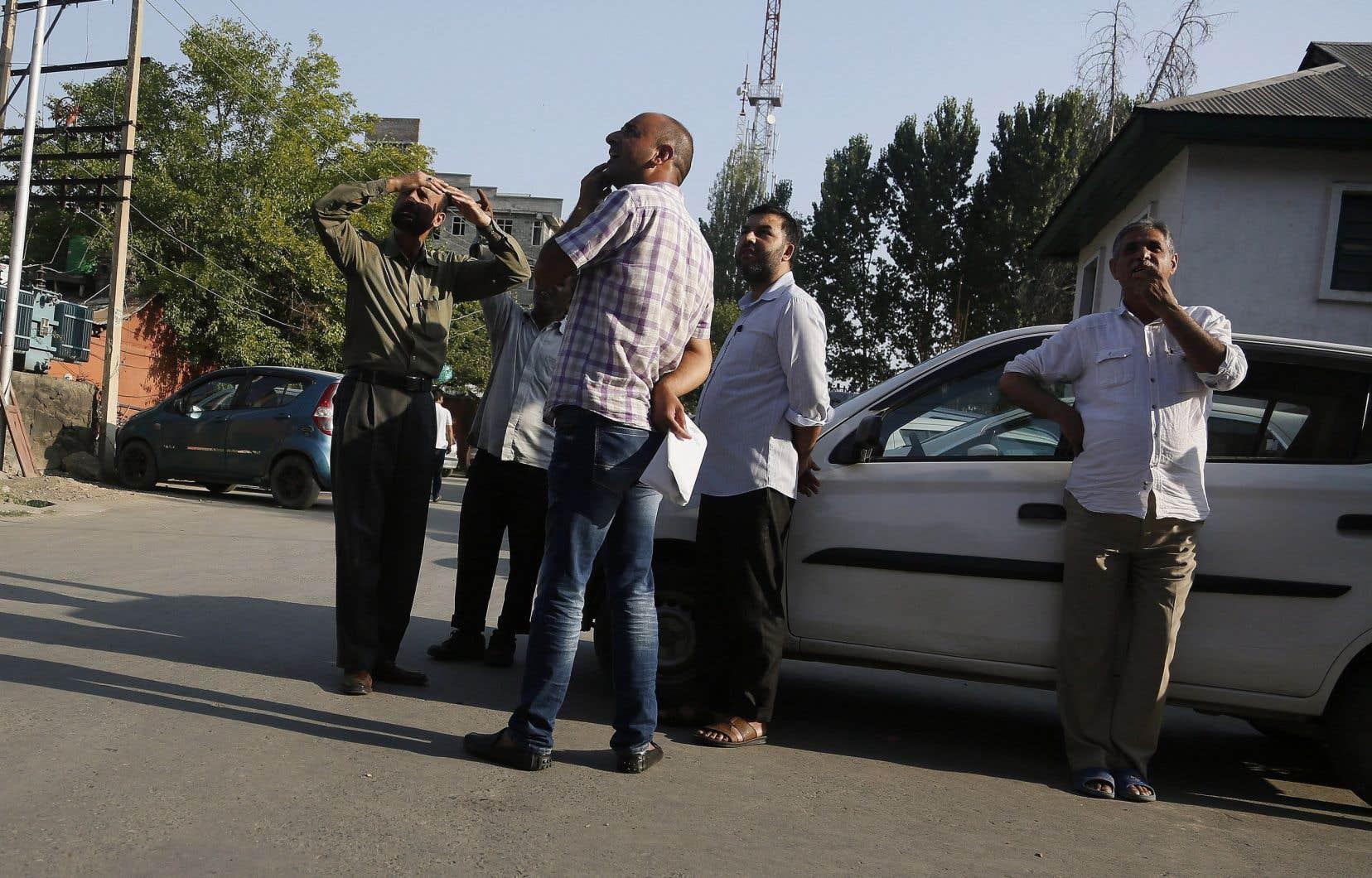 Des hommes jettent un œil en direction des immeubles à la suite du séisme qui a frappé mardi après-midi l'est du Pakistan.
