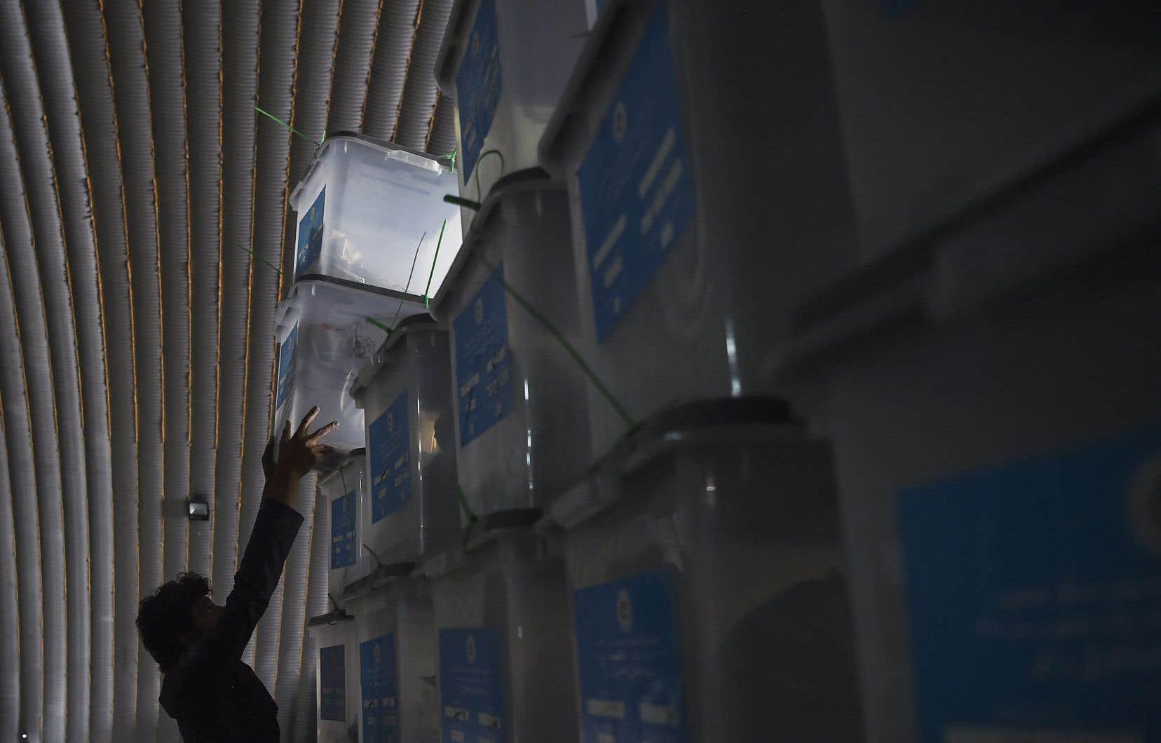 Un ouvrier de la Commission électorale indépendante (CEI) dépose des urnes dans un entrepôt le lendemain de l'élection présidentielle en Afghanistan, à Kaboul le 29 septembre 2019.