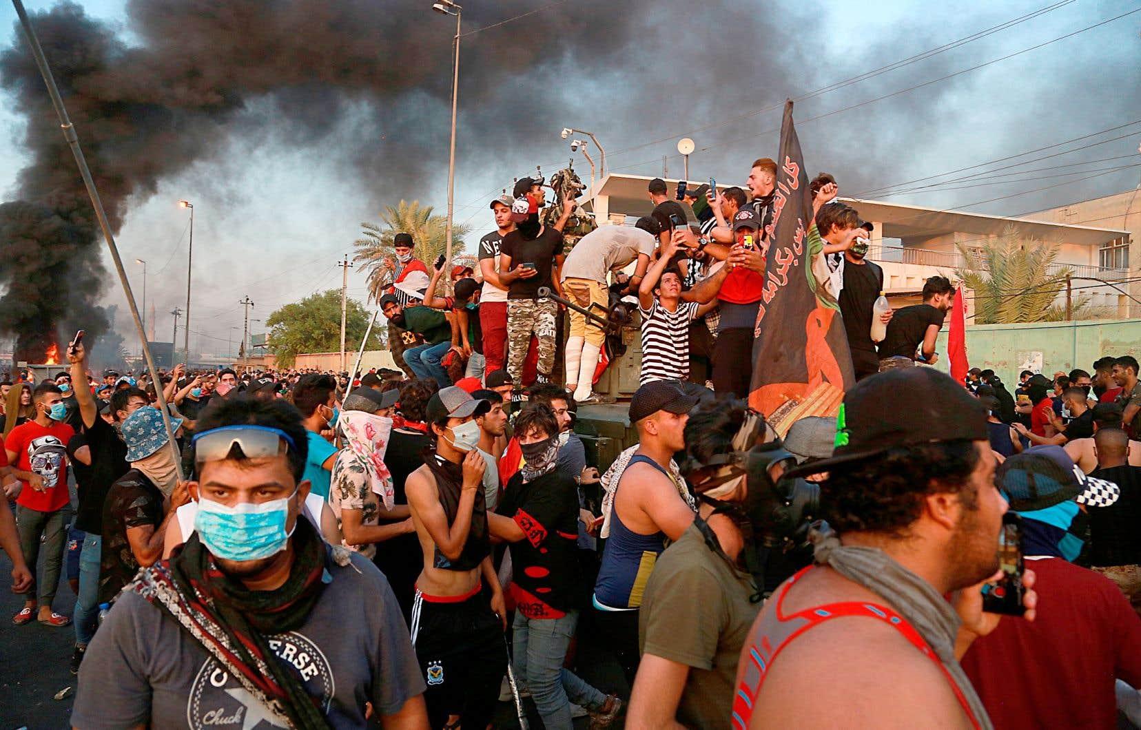 Des protestataires ont capturé un véhicule blindé avant de l'incendier, jeudi, au cours d'une manifestation à Bagdad.