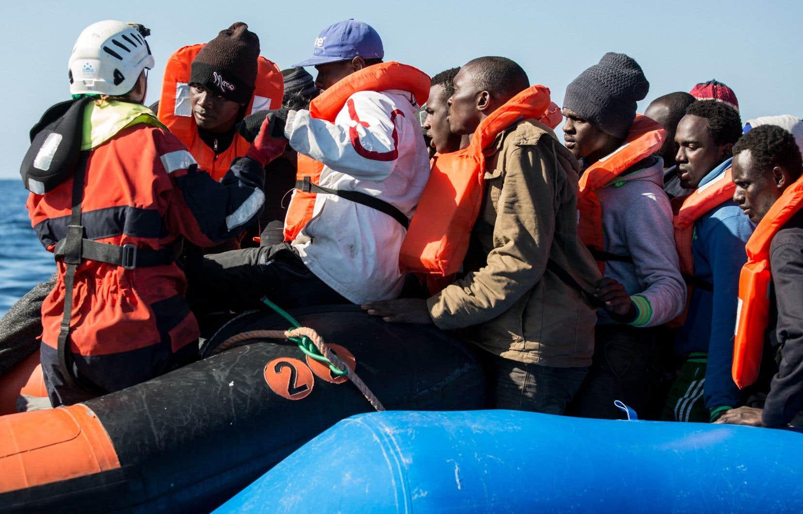 Un groupe de migrants reçoit l'aide d'une équipe Sea Watch, qui vient en aide aux personnes tentant de traverser la Méditerranée.