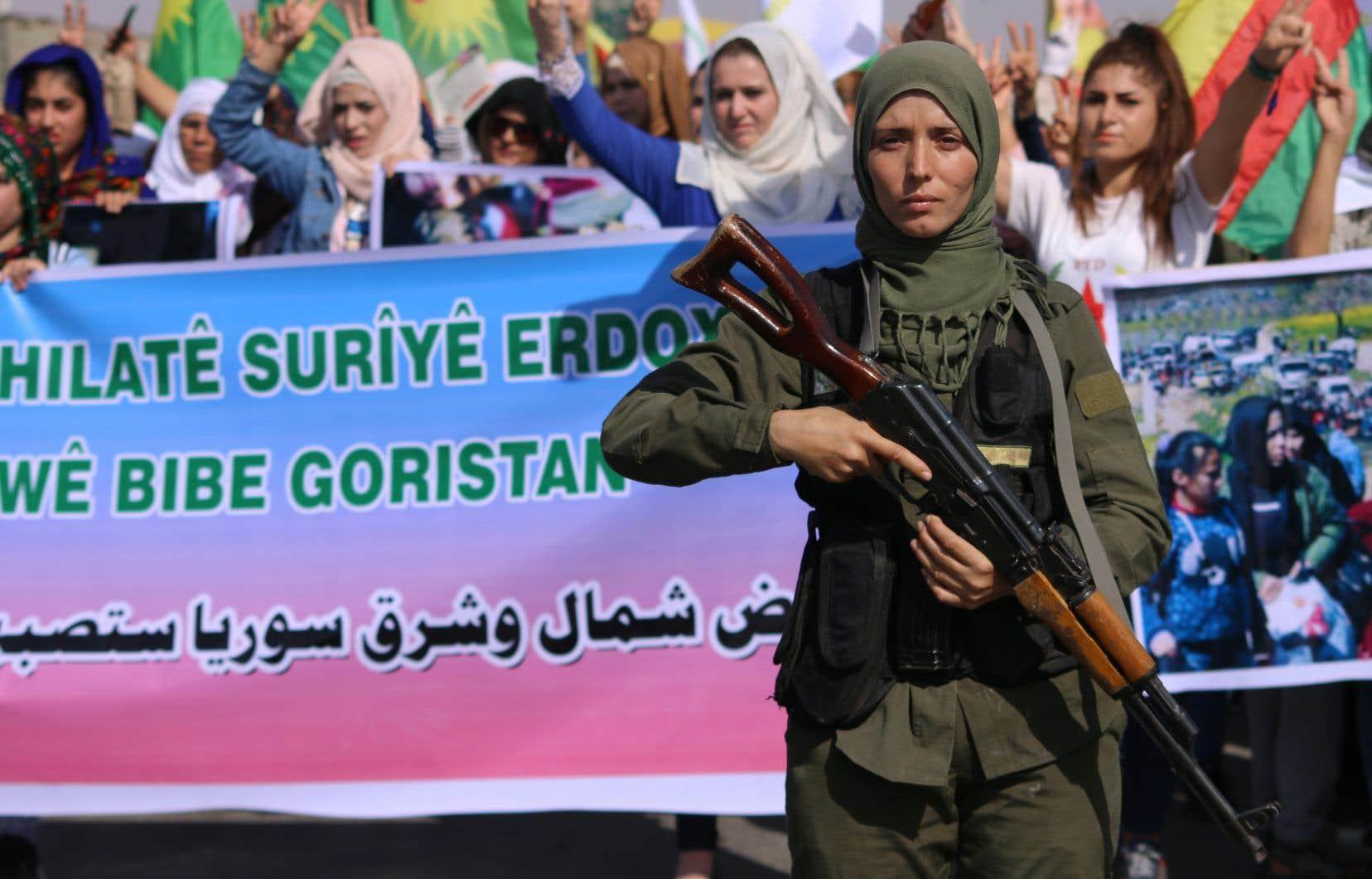Un membre de la Force de sécurité intérieure kurde monte la garde lors d'une manifestation dans la ville syrienne de Hassaké contre les offensives turques perpétrées dans des villes contrôlées par les Kurdes.