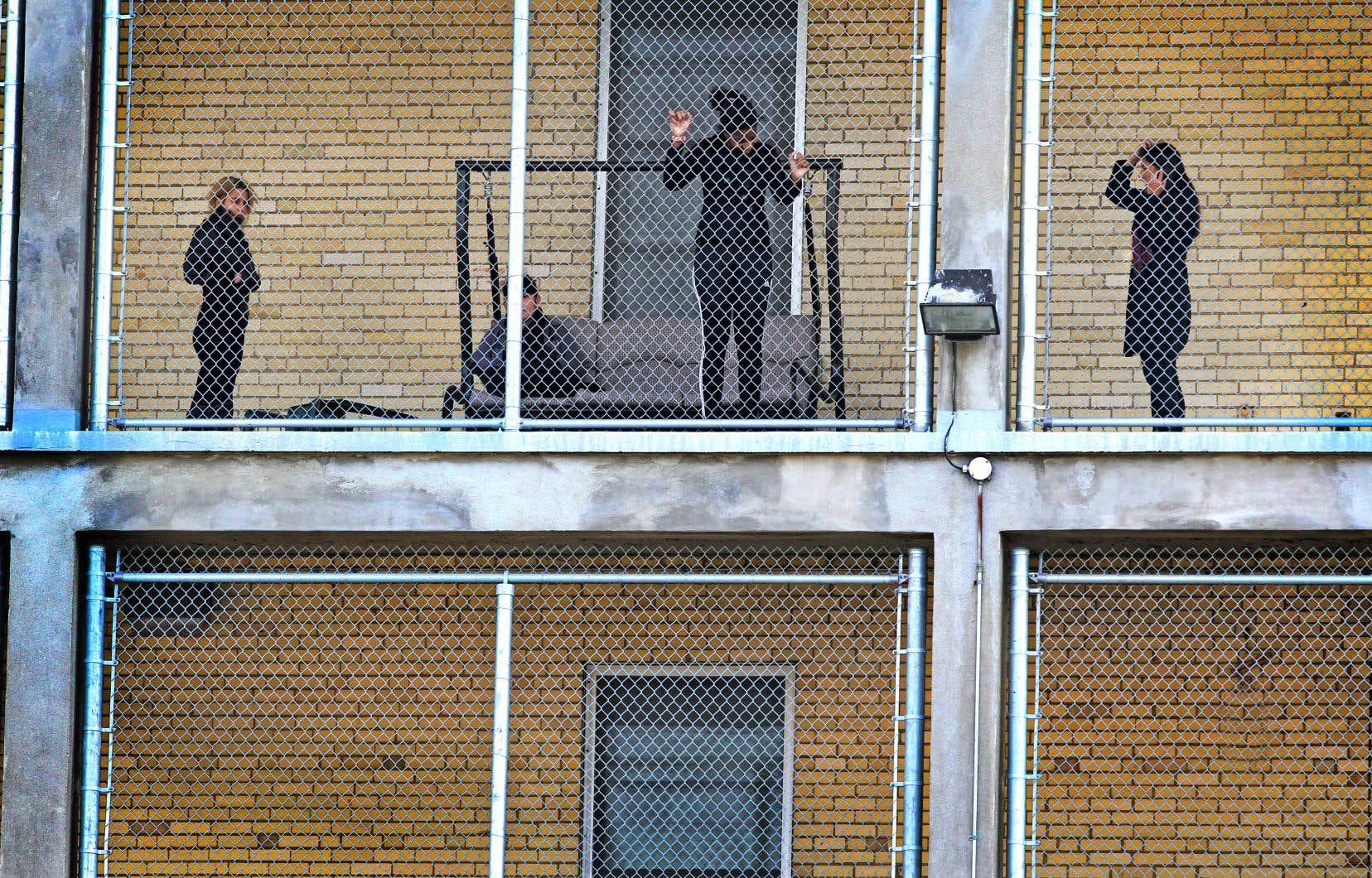 Des jeunes confiés au centre jeunesse à Laval prennent l'air sur un balcon grillagé.