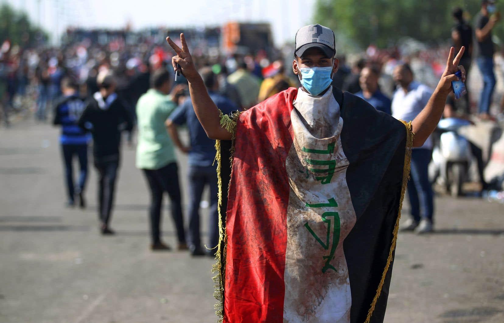 Un manifestant, entouré du drapeau irakien, fait le signe de victoire pendant le mouvement de contestation du samedi 26 octobre.