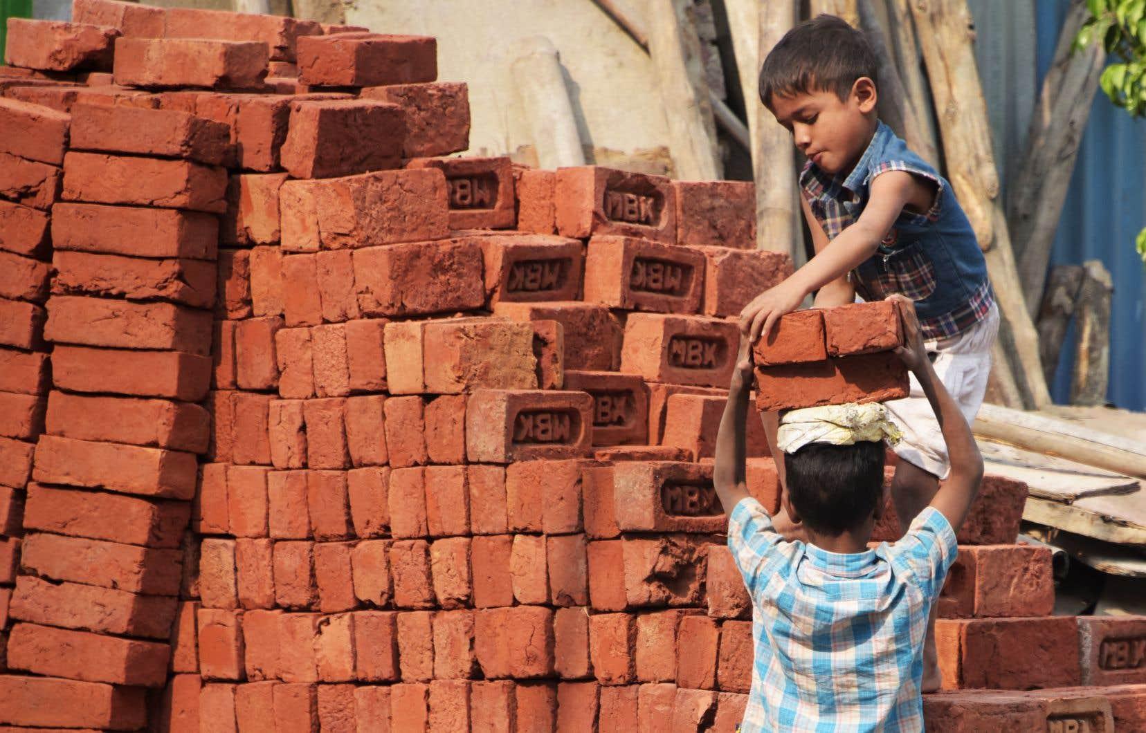 Des enfants travaillant sur un chantier de construction à New Delhi, la capitale indienne.  Il est très difficile pour une femme d'accéder à un emploi en Inde, ce qui ouvre grand la porte  à l'exploitation des enfants.