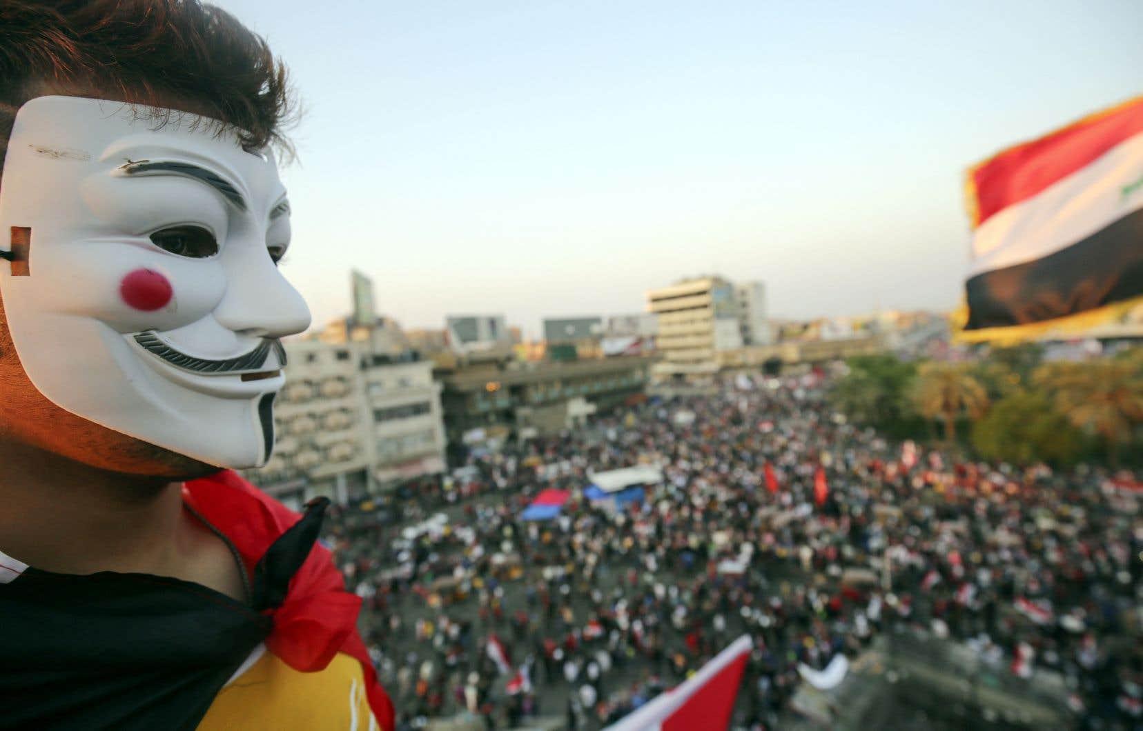 Un manifestant portant un masque de Guy Fawkes a pris part, jeudi, à un rassemblement sur la place Tahrir, à Bagdad.