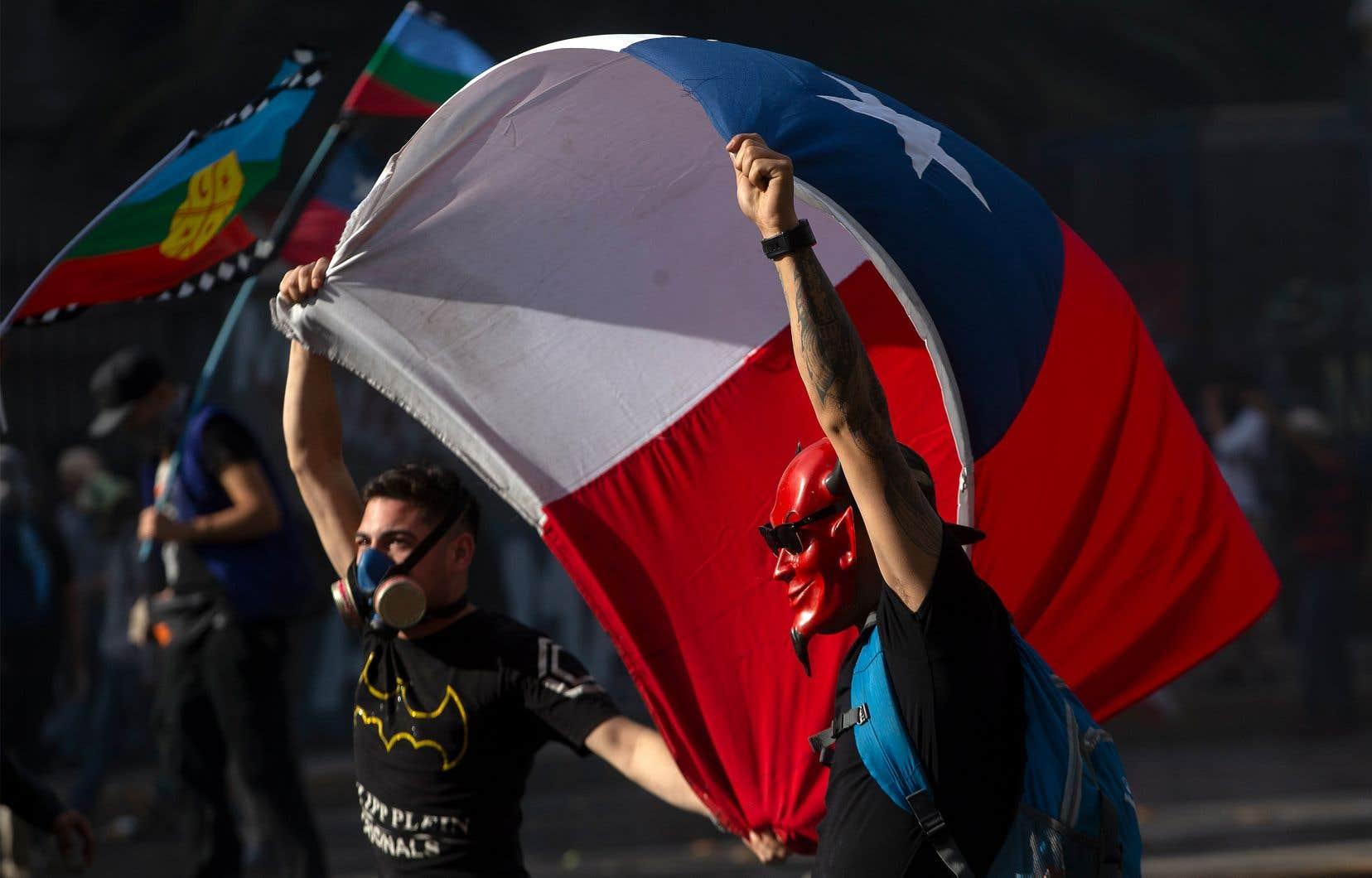 Des contestataires brandissaient un drapeau chilien dans une manifestation contre les politiques économiques du gouvernement, le 29 octobre, dans les rues de Santiago.