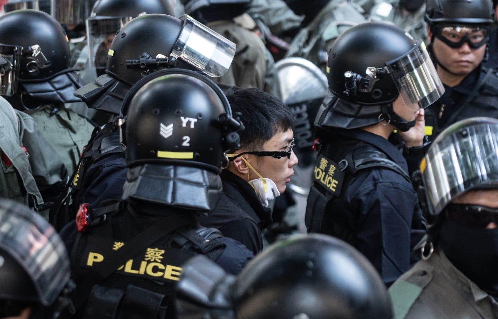 Un homme est escorté par la police alors qu'une manifestation s'est organisé dans le district de Tsim Sha Tsui à Hong Kong.