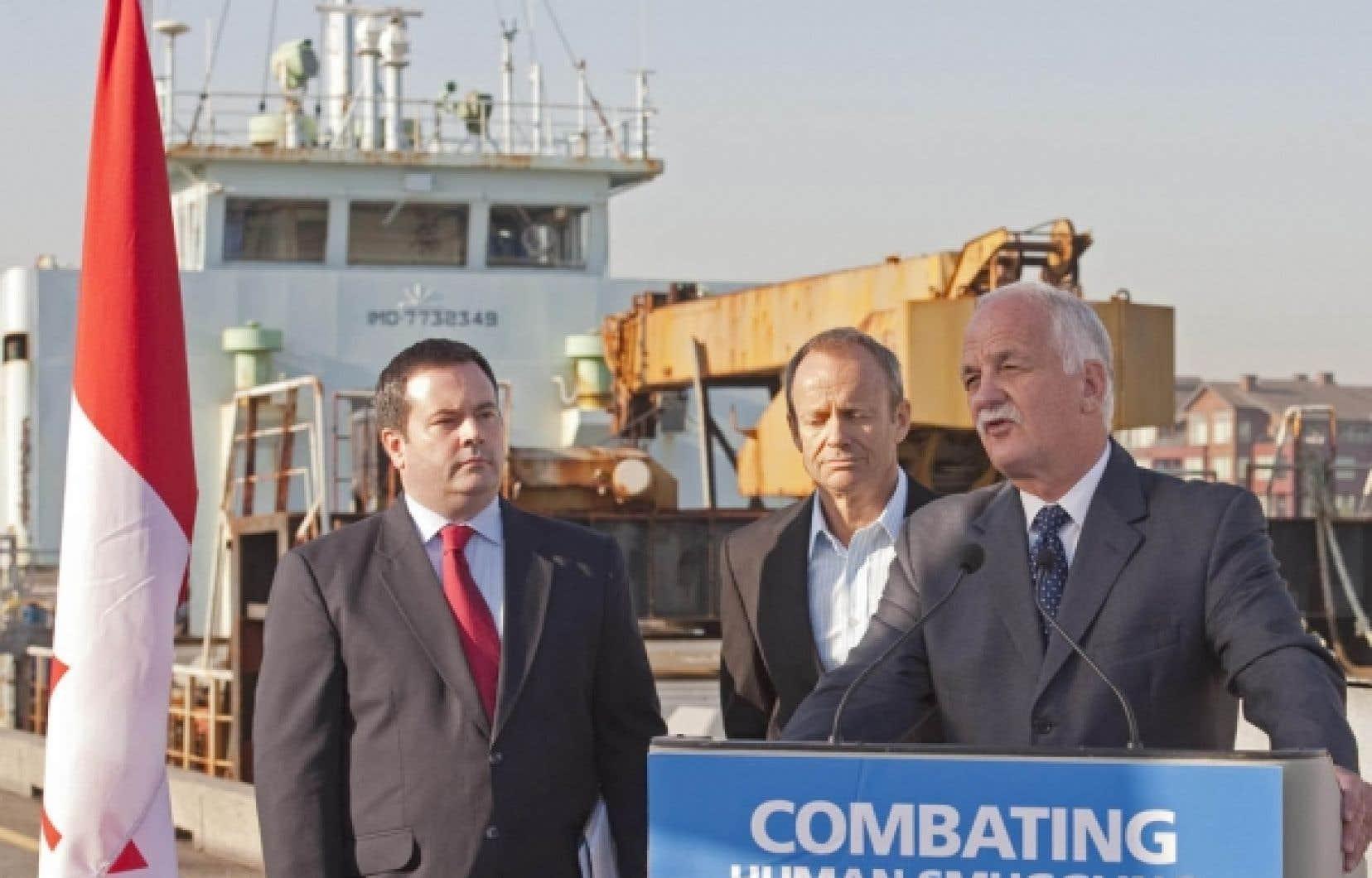 Les ministres Vic Toews (à droite), Jason Kenney (à gauche) et Stockwell Day ont dévoilé hier en Colombie-Britannique les détails du nouveau projet de loi. Derrière, le bateau à bord duquel sont arrivés 76 demandeurs d'asile tamouls en octobre 2009.<br />