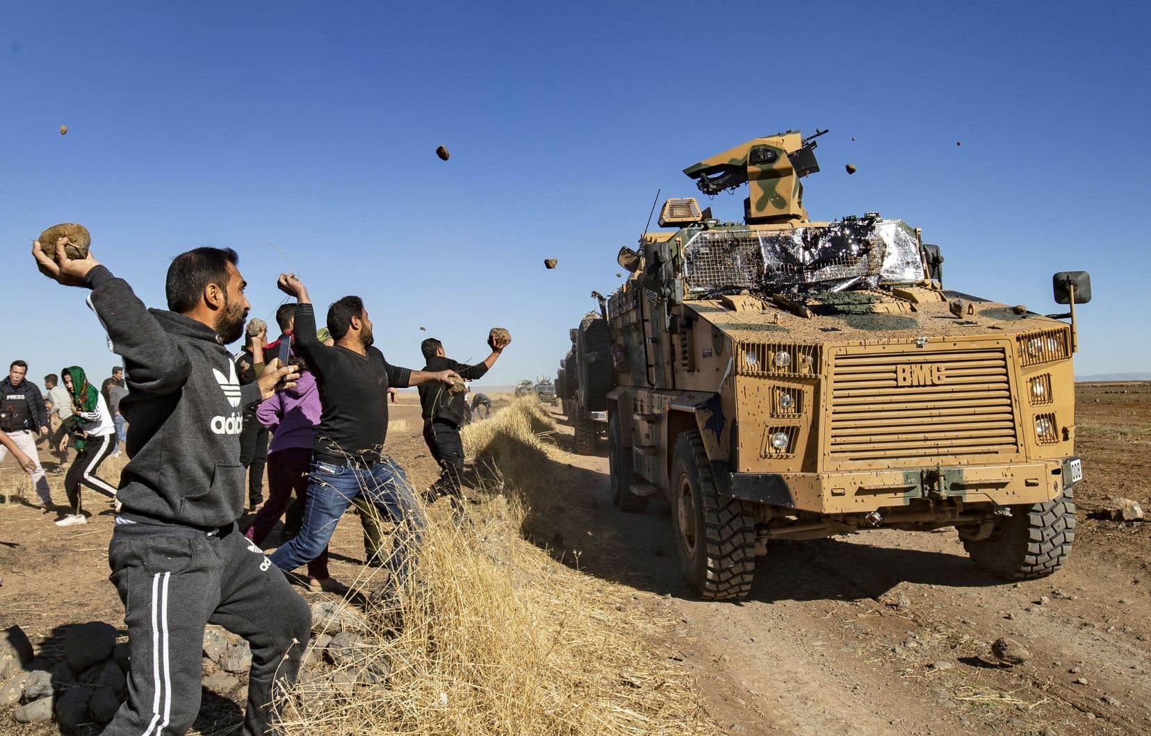 Un petit groupe de Kurdes s'est rassemblé près de la localité de Maabda, non loin de la frontière avec la Turquie, lançant pierres et chaussures sur le convoi.