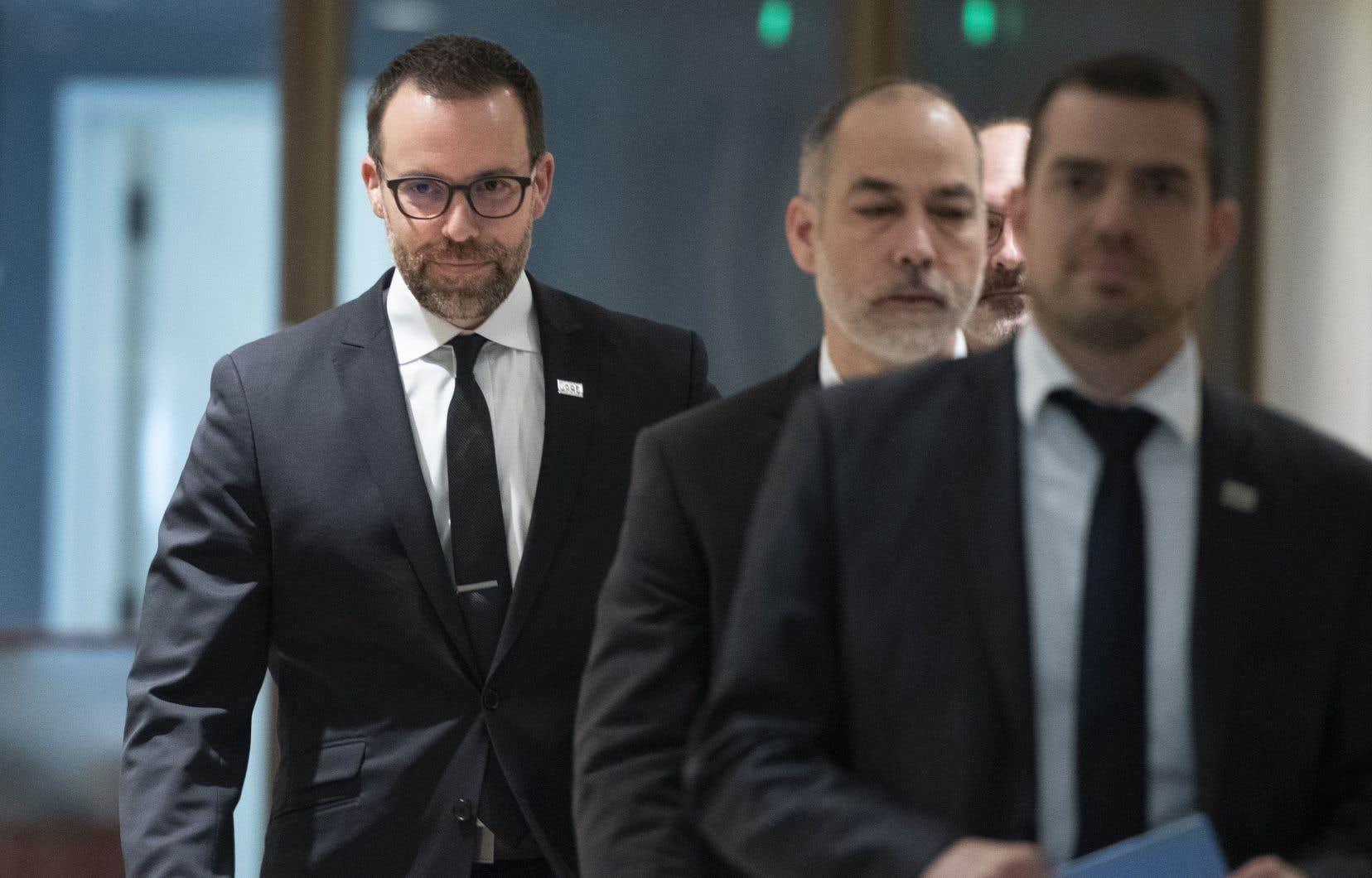 Le commissaire à la lutte contre la corruption, Frédérick Gaudreau, à l'arrière-plan, a annoncé mercredi la fermeture de l'enquête «Justesse», qui visait à démêler les allégations de malversation à la Société immobilière du Québec.