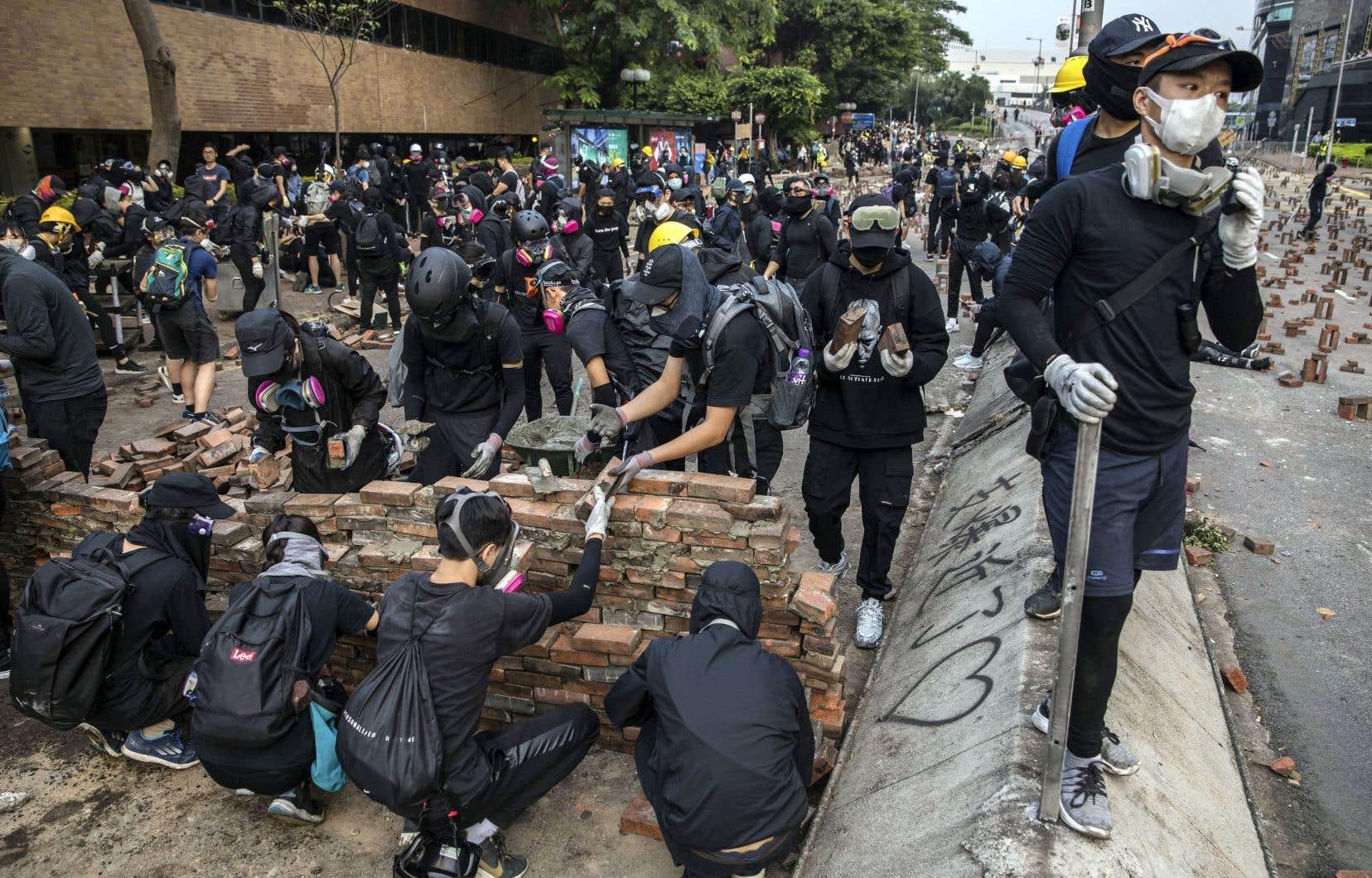 Des contestataires construisaient des barricades, jeudi, sur la route menant à l'Université Polytechnique de Hong Kong.