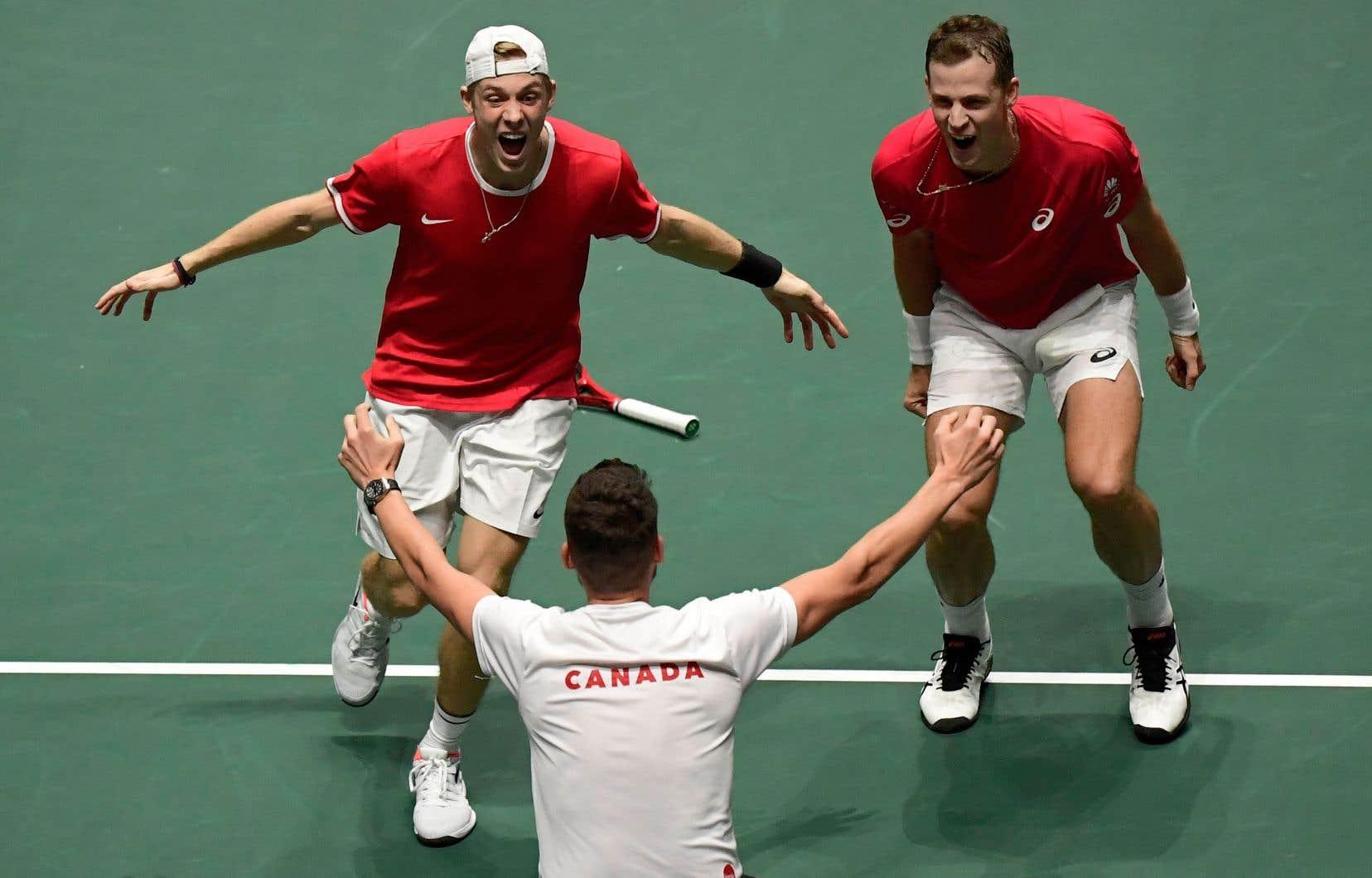 Denis Shapovalov et Vasek Pospisil célèbrent la victoire canadienne avec le capitaine de l'équipe, Frank Dancevic.